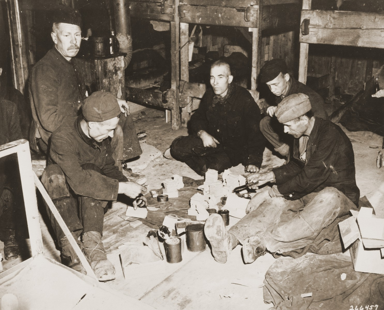"""A group of Soviet POWs share rations in the newly liberated Hemer POW camp.  Original caption: """"These gaunt-faced Soviets share a 10-in-1 ration supply kit furnished by men of a unit of the 75th Infantry Division, U.S. Ninth Army.  Soviet doctors at the camp say many of the inmates will die from malnutrition, tuberculosis, dysentery, and typhus.  Approximately 22,000 men were in the camp when it was liberated by the U.S. Army."""""""