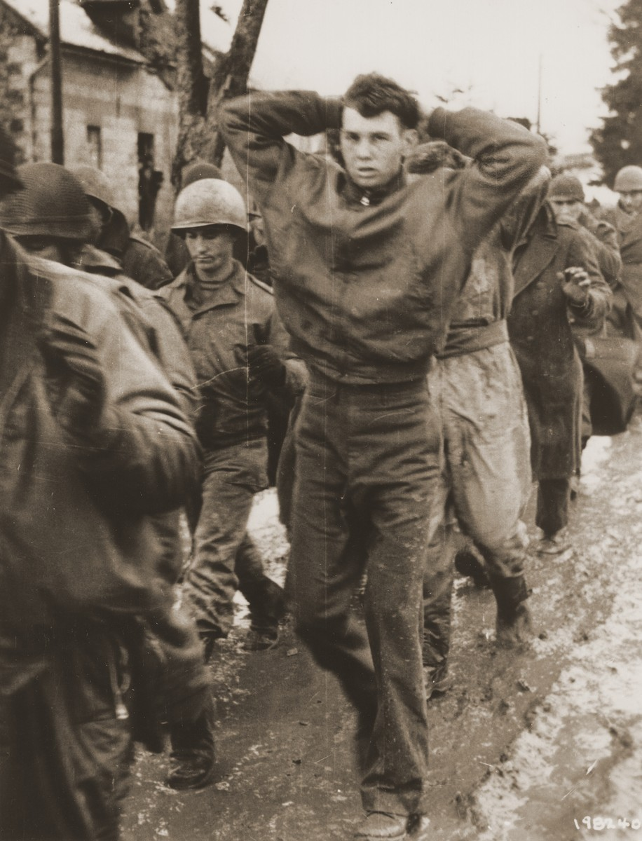 An American soldier, with his hands clasped behind his head, leads a file of Allied POWs captured by German troops during their mid-winter offensive on the western front.