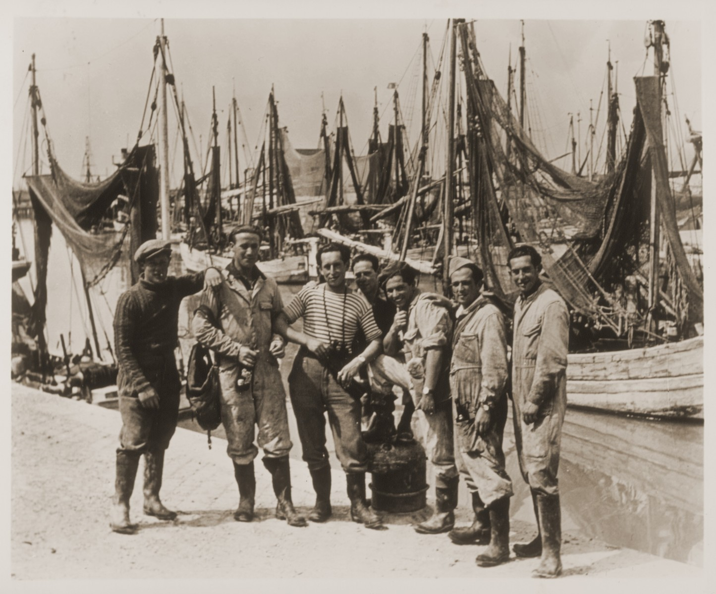 Jewish youth living at the Harishona Zionist collective in Fano, pose on a wharf where dozens of fishing boats are moored.  Pictured from left to right are: Yossef Ackerman, Patt, Daniel Serchuk, unknown, Yuzek Kempler, unknown, and Holtzman.