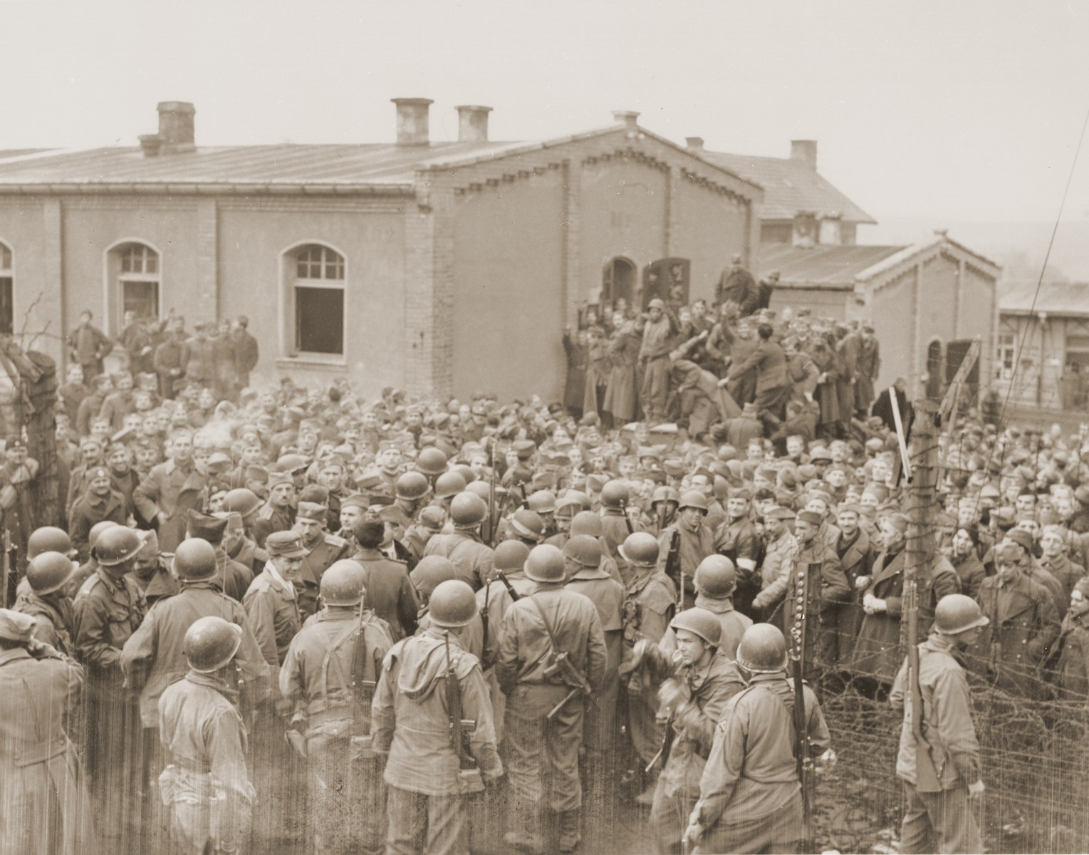 Allied prisoners in the Hammelburg POW camp greet their American liberators, who are from the 14th Armored Division.