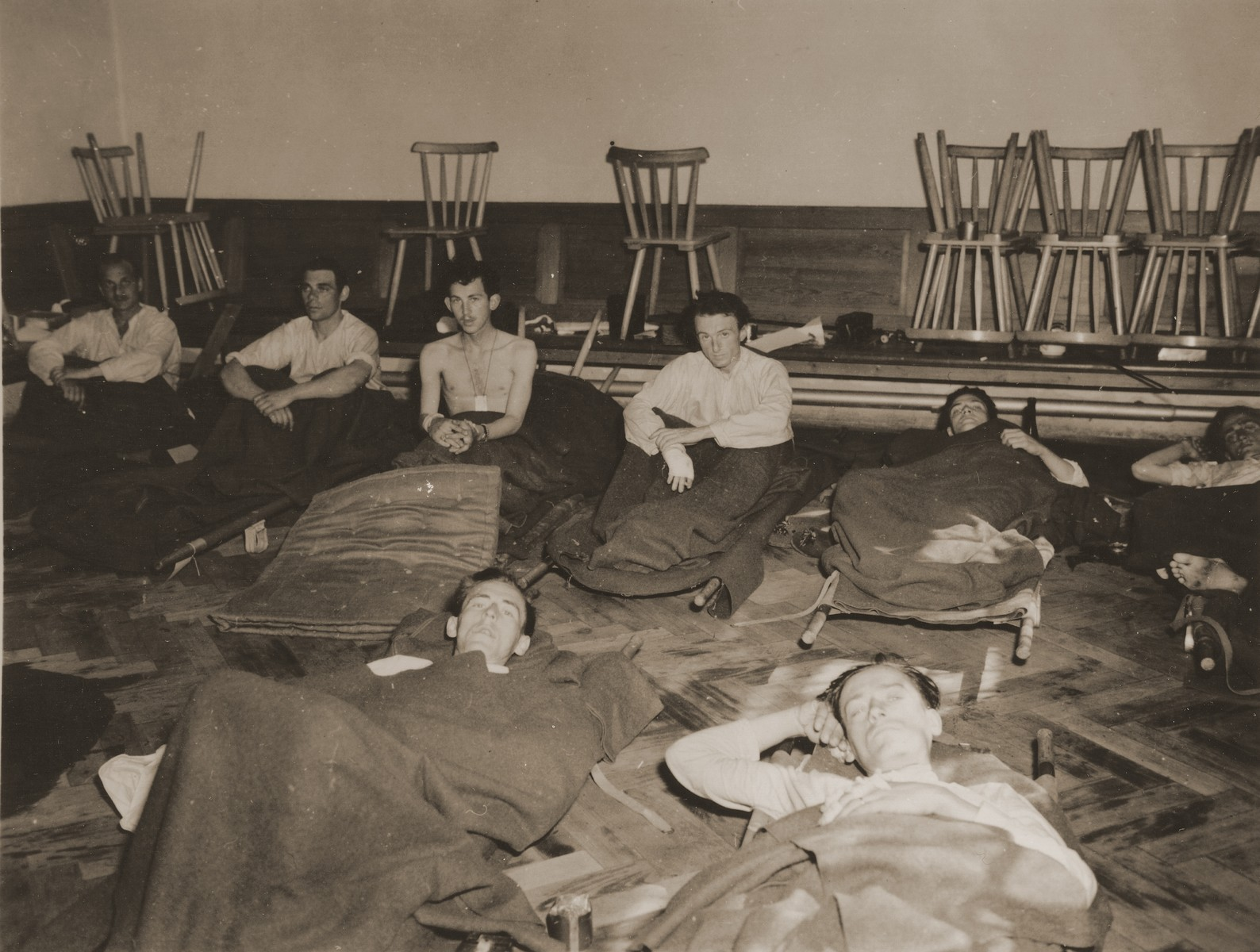 American POWs who survived a death march from the Berga concentration camp, recuperate at a U.S. Army hospital in Cham, Germany.  Gerald Daub is sitting up in the back row, second from left.  Peter Iosso is lying on the stretcher, top right.  Also pictured is Richard S. Kellogg.