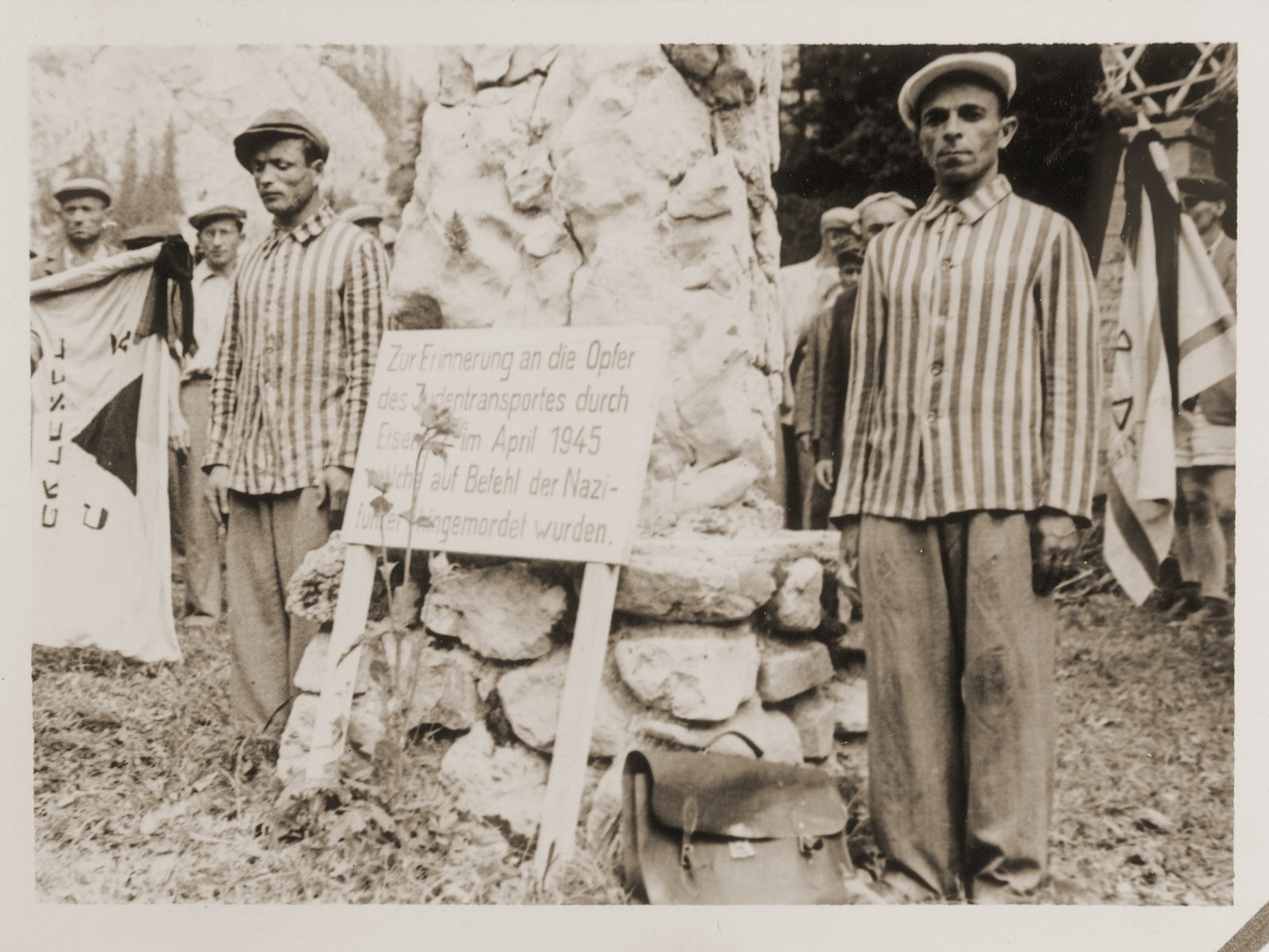 "Two men wearing striped prisoner uniforms stand next to a monument memorializing Jewish transports that passed through Eisenerz.   Family album bearing the title ""Motoring/Jewish DP camp/St. Marein [Sankt Marien]/School,"" that belonged to Moritz Friedler.  In 1946 and 1947, he served as a social worker with the Jewish Committee for Relief Abroad at the Sankt Marien DP camp in the British zone of Austria. Friedler subsequently became the JDC's Area Director in Linz, Austria.  The photo album documents Jewish DP life in both places."