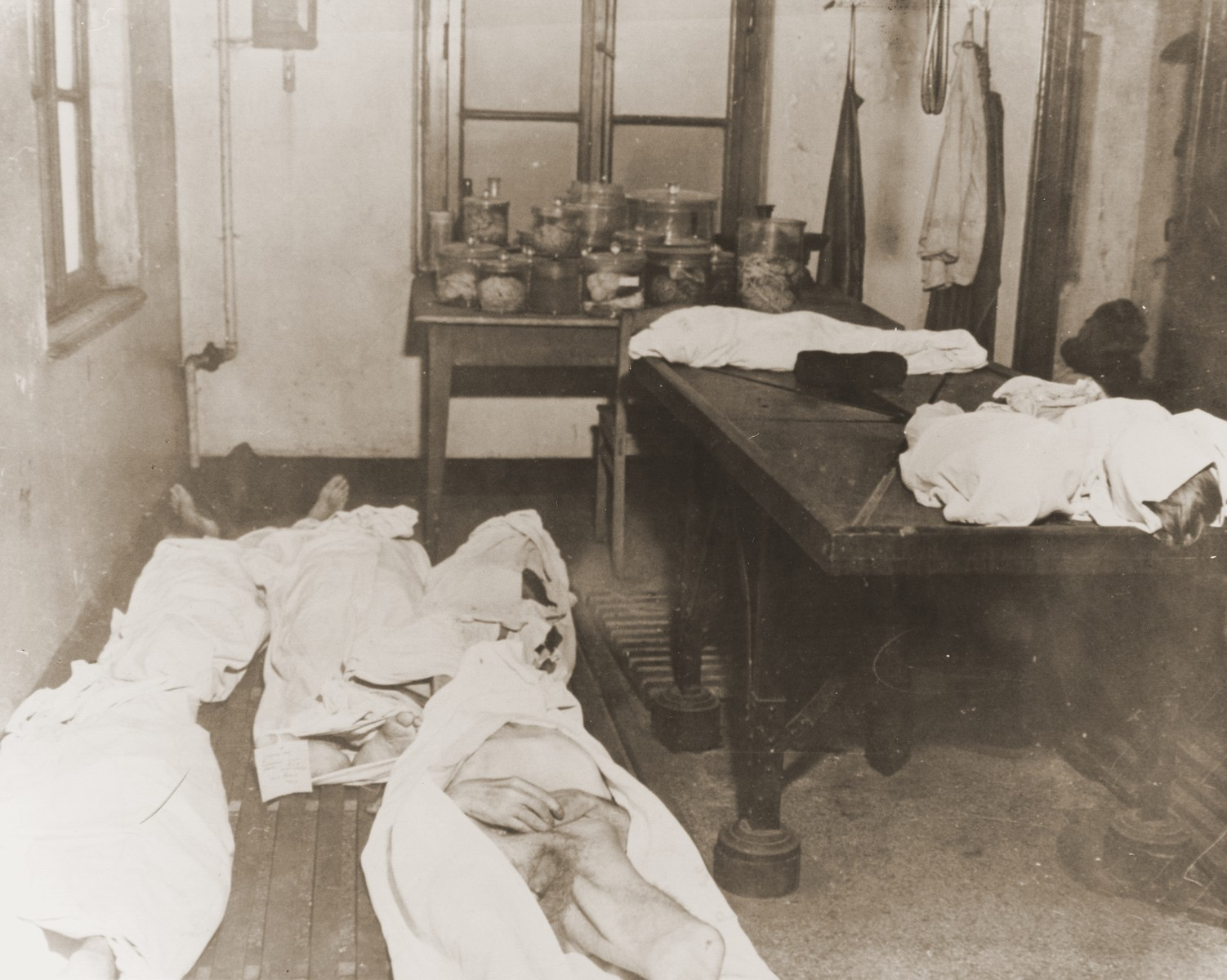 "Sheets cover the bodies of slave laborers found in a room in the Dortmund POW camp.  On the table are the bodies of four young children.  The original Signal Corps caption reads, ""U.S. TROOPS LIBERATE 4,070 MALTREATED PRISONERS IN DORTMUND.   When Ninth U.S. Army troops captured Dortmund, Germany, April 14, 1945, they liberated 4,070 prisoners and slave laborers of 13 nationalities--men, women and children.  The Americans discovered prisoners-of-war and workers too weak from starvation, malnutrition and disease to move.  Dozens were found lying in manure piles, ditches and cellars, dying from neglect and lack of medical treatment.  Fifty bodies were found in the yard of the German guard barracks, now used as a hospital, unburied and decomposing.  These people are now being cared for at the displaced persons center in Dortmund under command of Captain William T. Drake of Wilmington, Ohio.  Two Russian doctors and Russian women assist medical corpsmen of the 79th Division of the Ninth Army in caring for them.  PNA                                                                    EA 64935  THIS PHOTO SHOWS:  Sheets cover the bodies of slave laborors and prisonerS-of-war.  On the table are four younG children  U.S. Signal Corps Photo ETO-HQ-45-34459. SERVICED BY LONDON OWI TO LIST B-1 CERTIFIED AS PASSED BY SHAEF CENSOR"