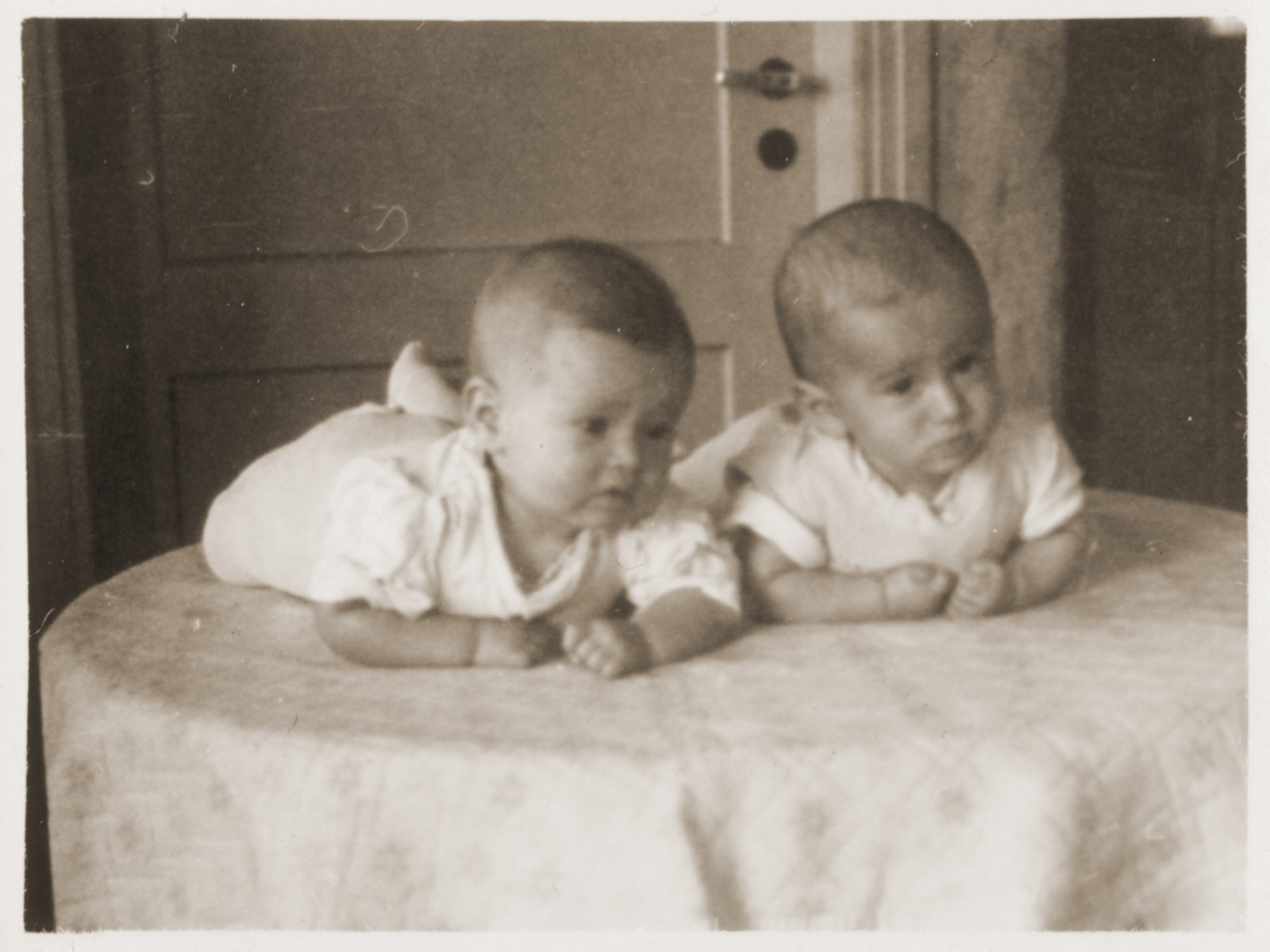 Twin Jewish DP infants lie on a table in the Bergen-Belsen displaced persons camp.  Pictured are Yaffa and Yitzchak Zyngier.  Their parents, Rachmiel and Eva Zyngier, were both were from Starachowice and were survivors of the Bergen-Belsen concentration camp.