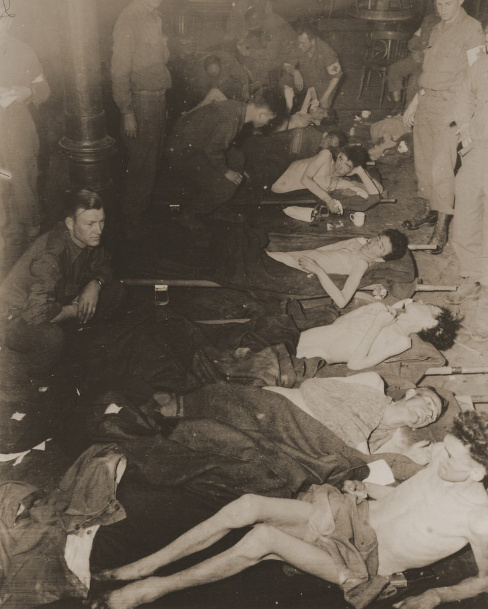 American medics treat 63 American POWs who survived a death march from the Berga concentration camp and were liberated by soldiers of the 357th Infantry Regiment.  From foreground to background: Pvt. Winfield Rosenberg, Pfc. Paul Capps, Pfc. James Watkins, Pvt. Alvin Abrams, and Pfc. Joseph Guigno. Also pictured is Pvt. Chester Sniegocki.