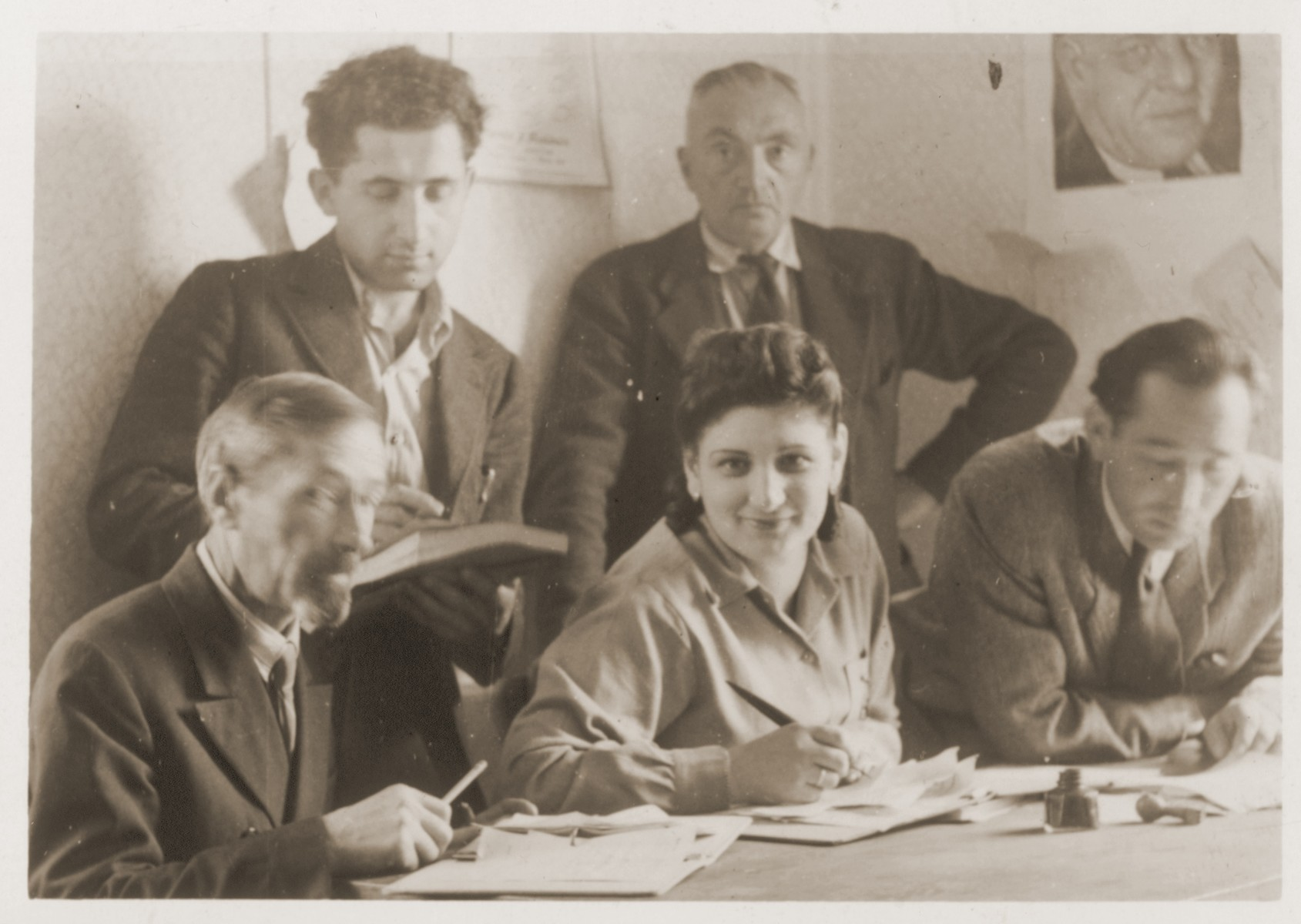 Members of the administrative staff of the Schlachtensee displaced persons camp pose in the office of UNRRA camp director Schwartzberg.  Shmuel (Miles) Lerman sits at the far right.