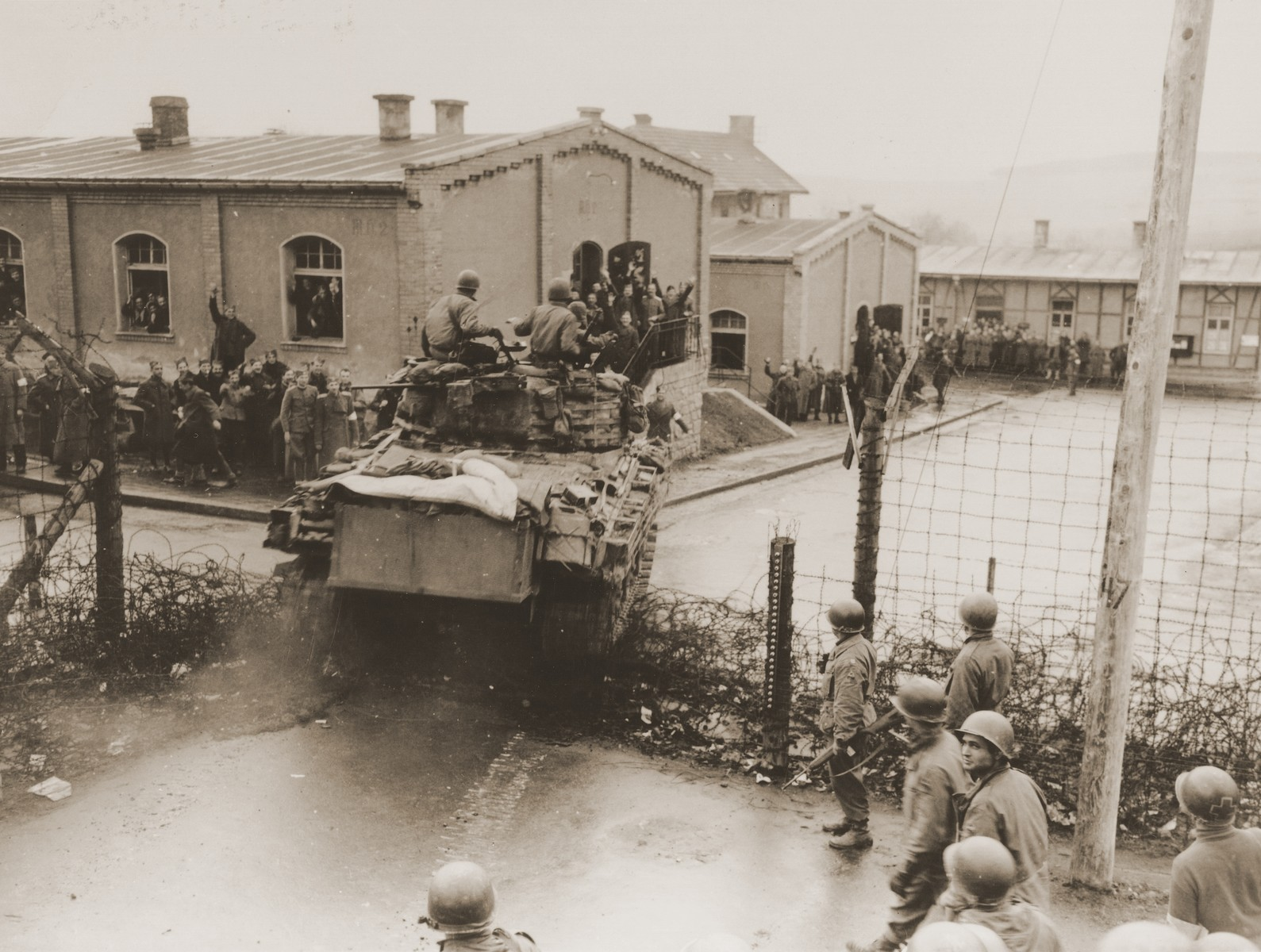 Allied POWs, imprisoned in a camp near Hammelburg, cheer as an American tank crashes through the barbed wire enclosure of the prison camp.