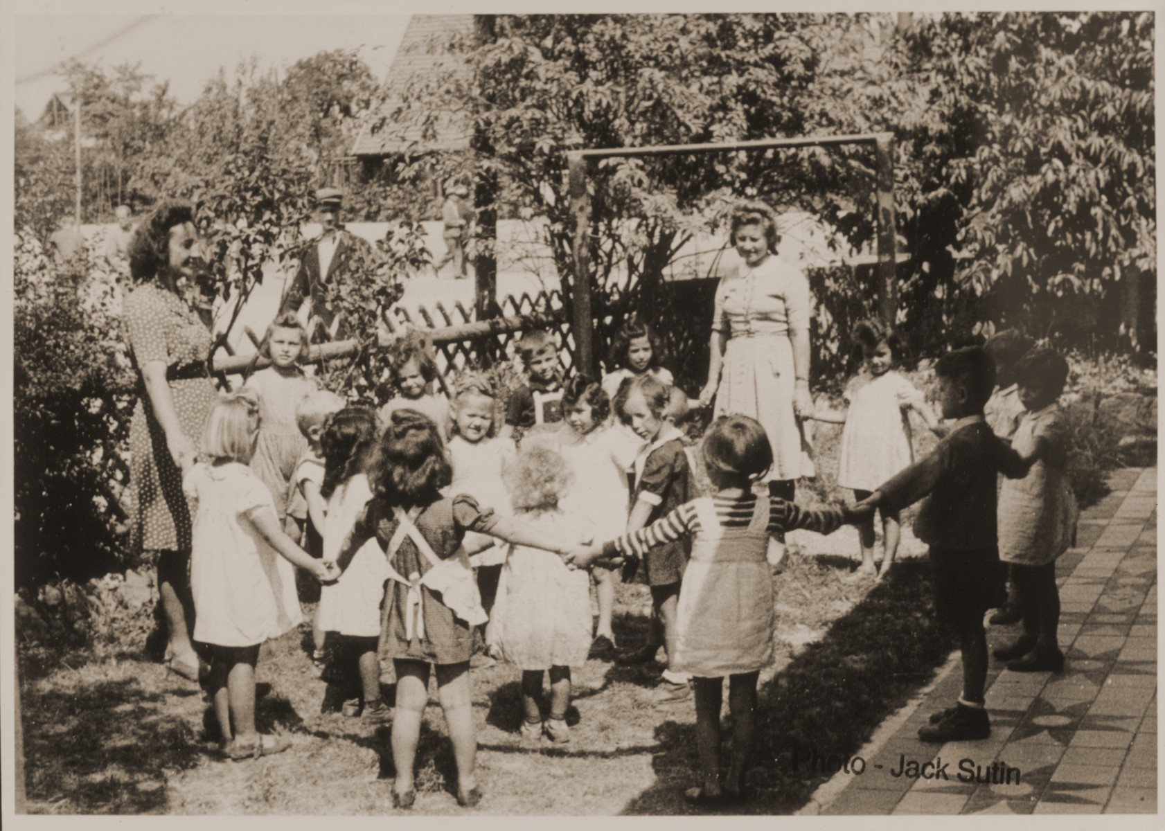 Children and their teachers play a circle game in the schoolyard at the Neu Freimann displaced persons camp.