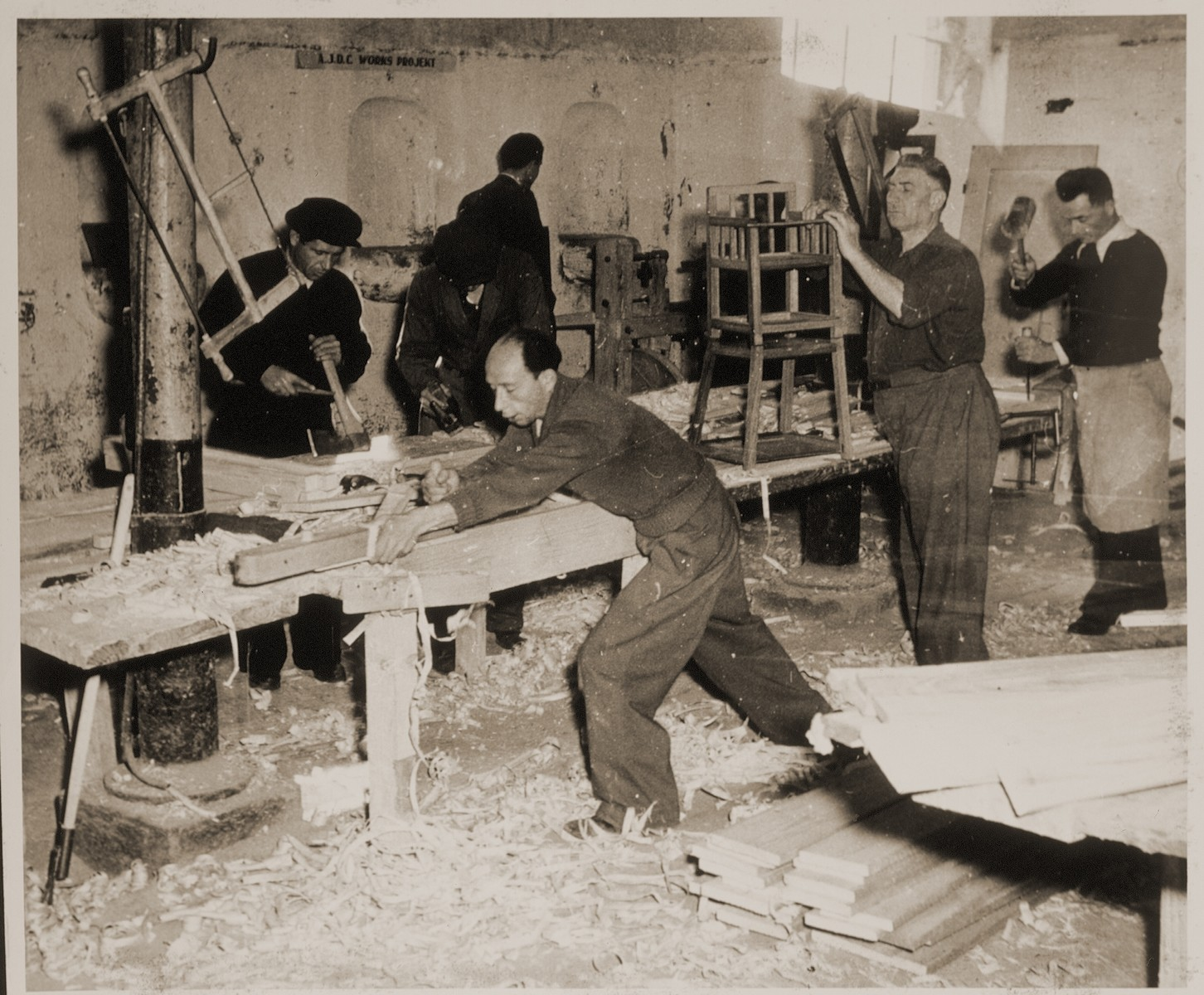 """Jewish DPs build chairs in a carpentry shop in the Bindermichl displaced persons camp.   Family album bearing the title """"Motoring/Jewish DP camp/St. Marein [Sankt Marien]/School,"""" that belonged to Moritz Friedler.  In 1946 and 1947, he served as a social worker with the Jewish Committee for Relief Abroad at the Sankt Marien DP camp in the British zone of Austria. Friedler subsequently became the JDC's Area Director in Linz, Austria.  The photo album documents Jewish DP life in both places."""