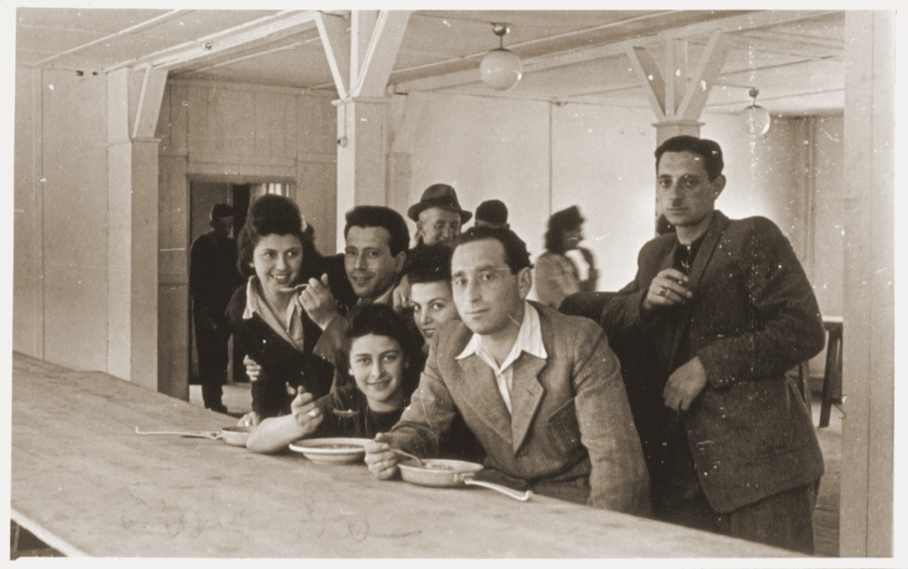 A group of Jewish DPs eat in the mess hall at the Schlachtensee displaced persons camp.    Seated with bowls before them are Shmuel (Miles) and Rozalia (Chris) Lerman.