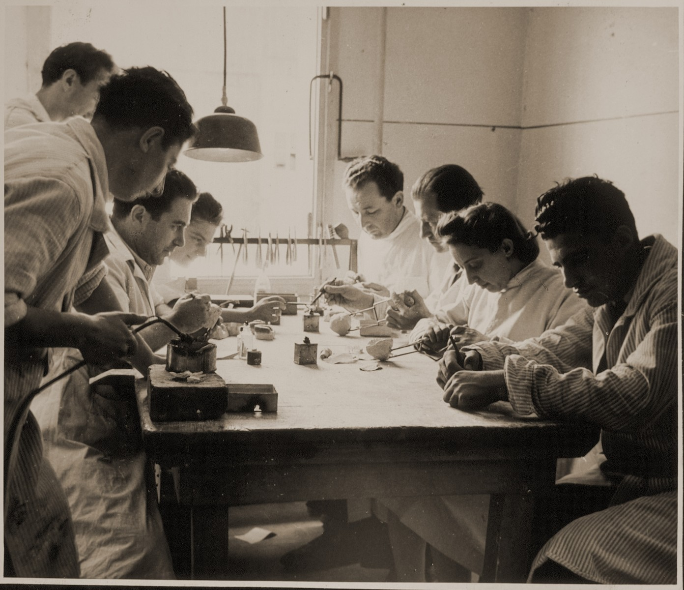 """Jewish DPs prepare dental molds in a dentistry vocational training class in Sankt Marien.   Family album bearing the title """"Motoring/Jewish DP camp/St. Marein [Sankt Marien]/School,"""" that belonged to Moritz Friedler.  In 1946 and 1947, he served as a social worker with the Jewish Committee for Relief Abroad at the Sankt Marien DP camp in the British zone of Austria. Friedler subsequently became the JDC's Area Director in Linz, Austria.  The photo album documents Jewish DP life in both places."""