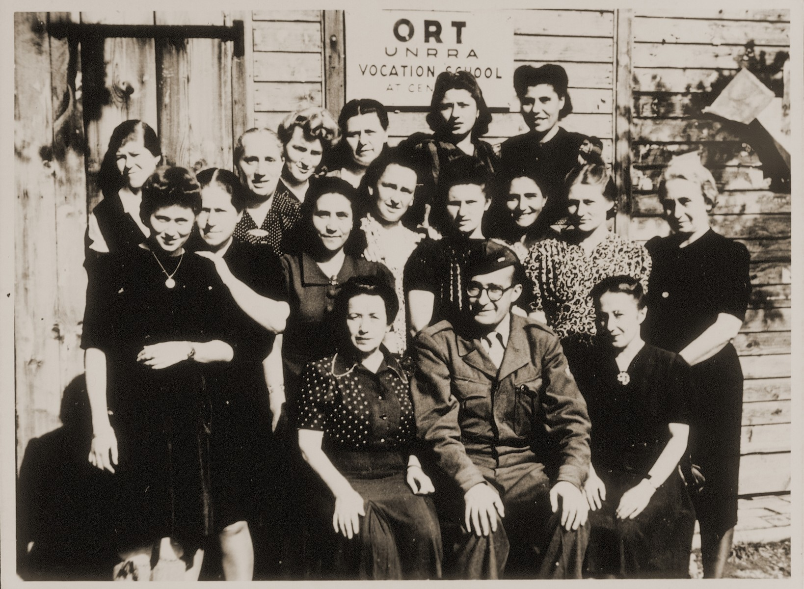 Group portrait of young Jewish DP women with their male instructor in front of an ORT (Organization for the Rehabilitation through Training) vocational training center in Germany.