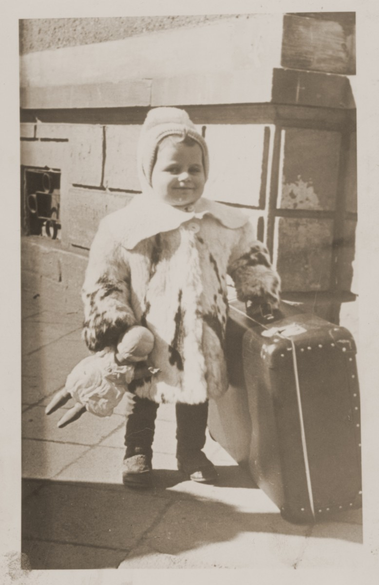 A young Jewish DP child wearing a fur coat and clutching a doll, poses next to a suitcase as her family prepares to depart from the Lampertheim displaced persons camp for the United States.  Pictured is Mirjam Kushelewicz.