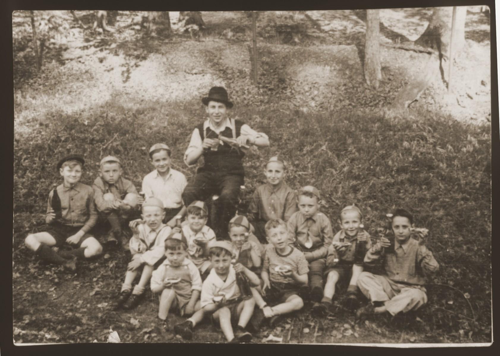 A teacher poses with his students from a Feldafing cheder on a picnic excursion.   The teacher is Meir Katz.  The children are Yaakov Stetsky, Alter Rothbart, Aaron Cukerman, Avrohom Strikovsky, Avrohom Rosenberg, Moshe Bertram. Meir Hose, Victor Schultz, Chaim Birnbaum, Wolf Strasberg, Chaim Frashkir, Leibe Bzshisky, and Mottel Sobolsky.