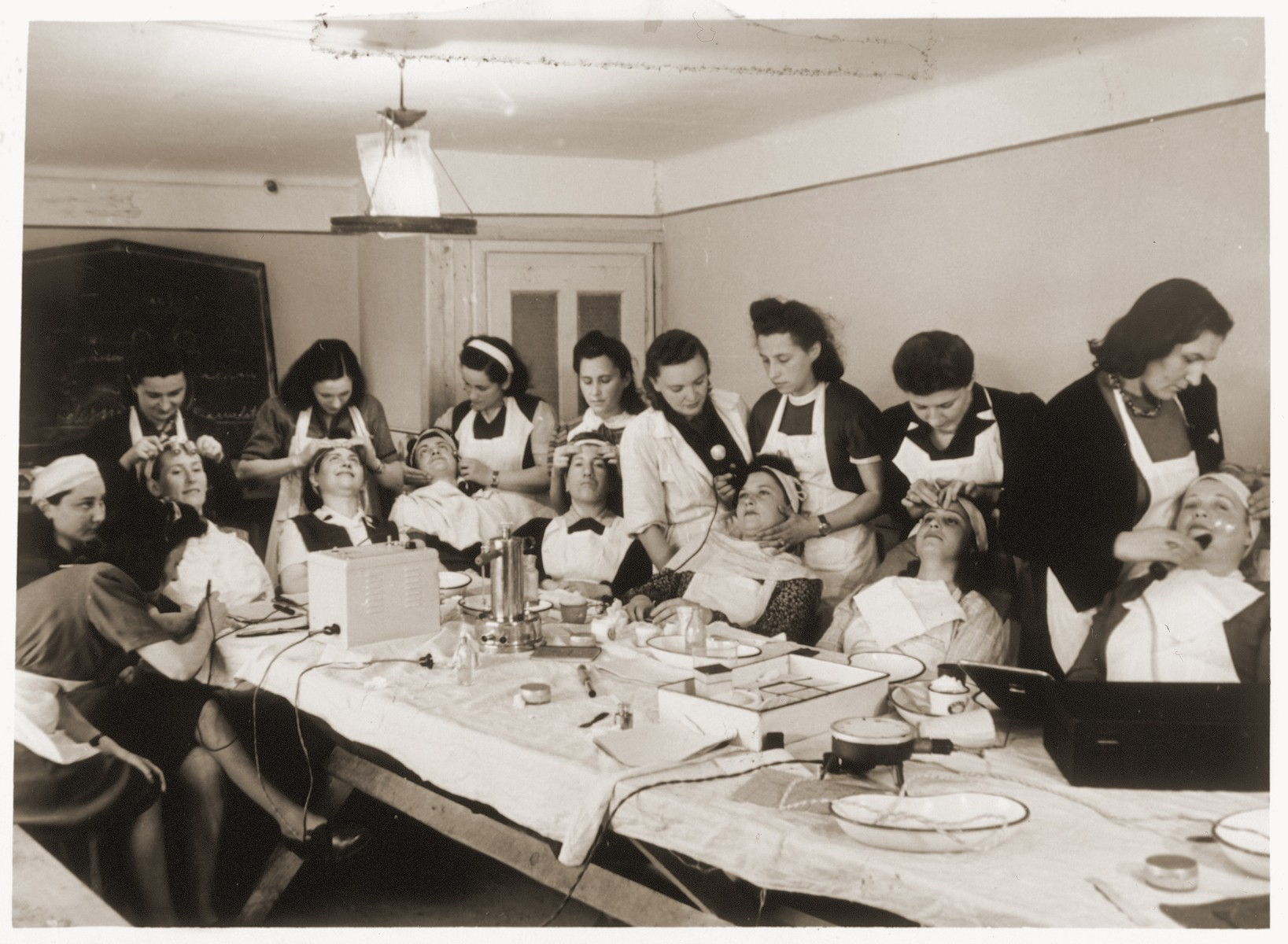 Women apply hair and facial treatments to each other in a cosmetology class in the Bindermichl displaced persons camp.  Pictured at the far right getting a facial is Sally Biederman.