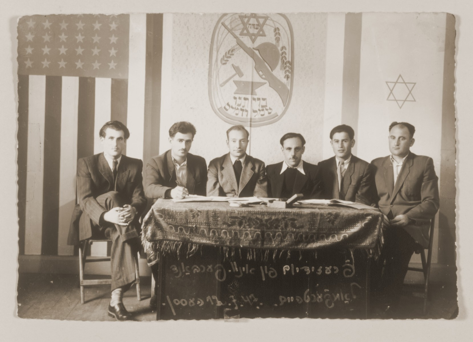 """Meeting of the six-member presidium of an association in the Lampertheim displaced persons camp.    The shield above the table bears the motto, """"Our covenant, toil and blood."""""""
