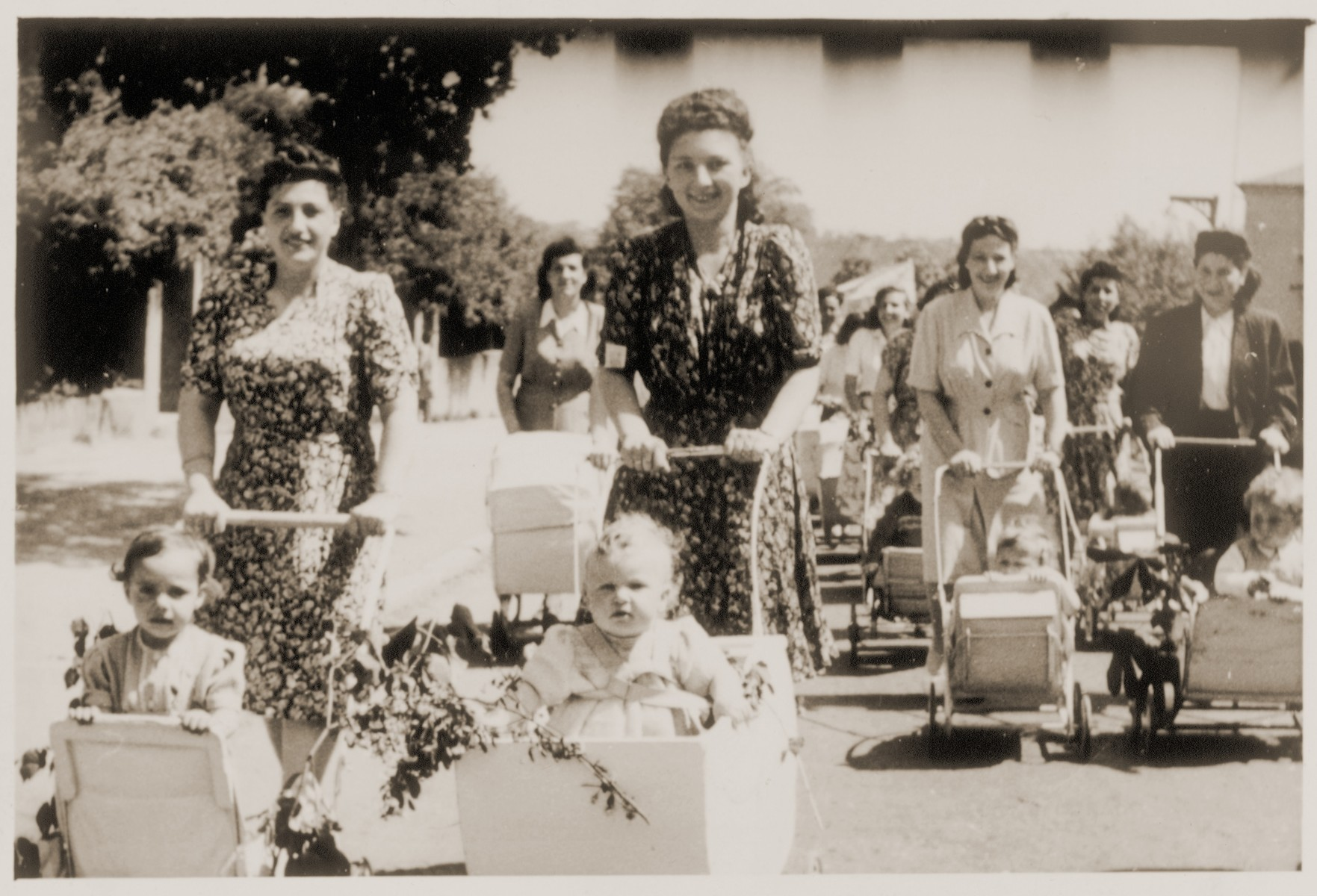 Young mothers take their babies for a stroll in the Landsberg DP camp.    Dorit Mandelbaum is pictured in the baby carriage on the left.  Her mother, Anka, is pushing the carriage.  Chava Oppenheim pushes her son Aviezer in the carriage, third from the right.  Also pictured is Laja Minc.