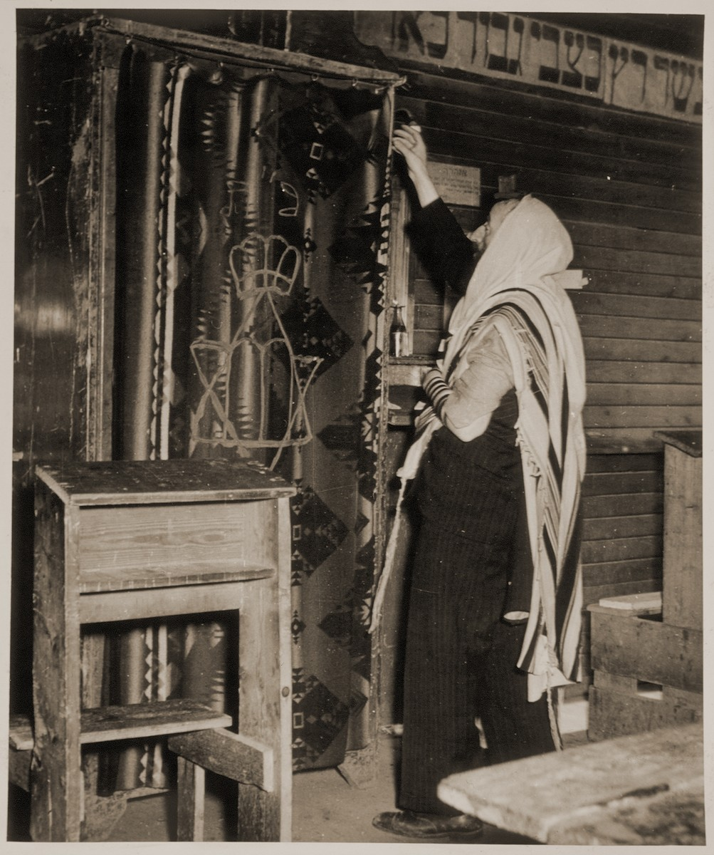 """A man wearing a prayer shawl and phylacteries stands in front of the Torah ark at a displaced persons camp in Sankt Marien, Austria.   Family album bearing the title """"Motoring/Jewish DP camp/St. Marein [Sankt Marien]/School,"""" that belonged to Moritz Friedler.  In 1946 and 1947, he served as a social worker with the Jewish Committee for Relief Abroad at the Sankt Marien DP camp in the British zone of Austria. Friedler subsequently became the JDC's Area Director in Linz, Austria.  The photo album documents Jewish DP life in both places."""
