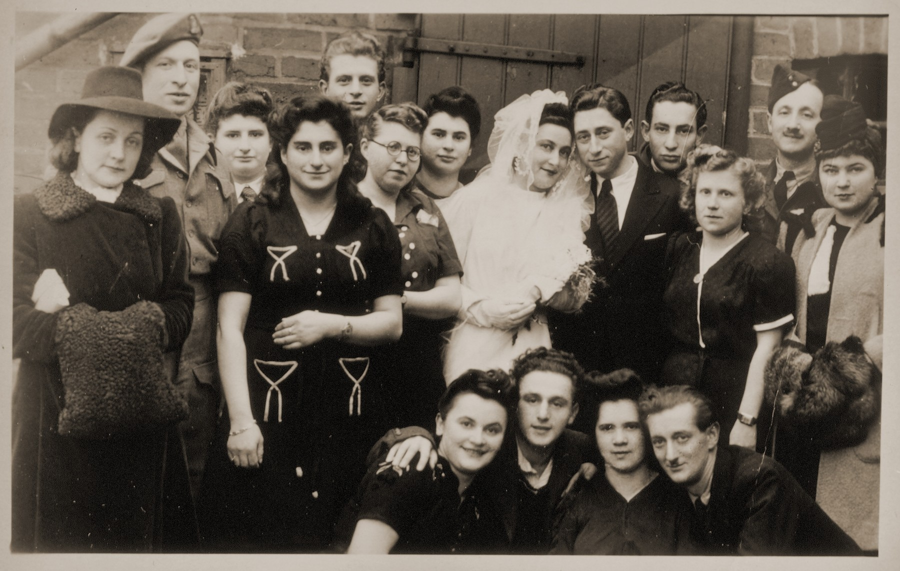 Joli Josef from Romania and Gerhard Cohn from Germany pose with their wedding guests in the Bergen-Belsen displaced persons camp.  Joli Josef is one of 17 to 20 in the Celle and Belsen DP camps who wore the gown that Lilly Friedman had made from an old German parachute her husband purchased for the purpose.