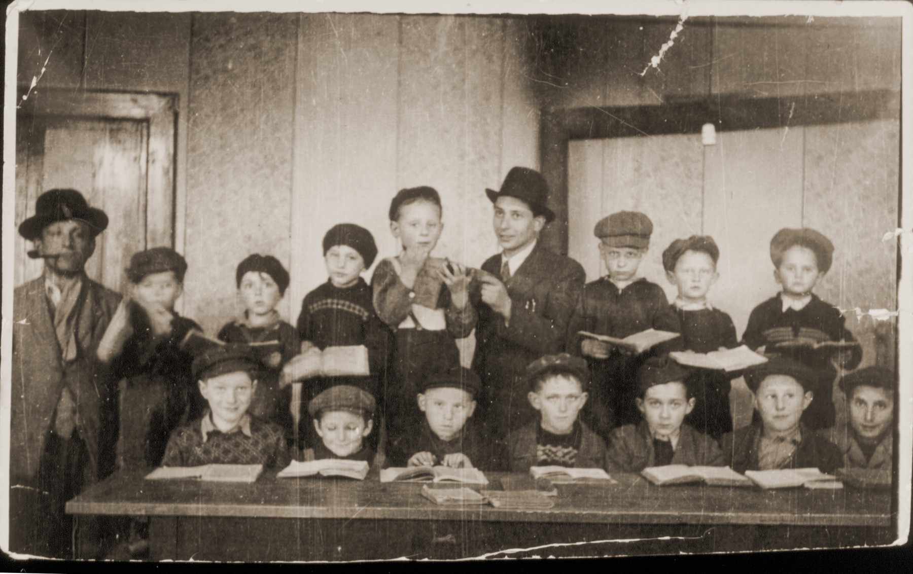 Group portrait of Jewish boys studying traditional Jewish texts at a religious school in the Feldafing displaced persons camp.  Seated from left to right are: Yaakov Stetsky, Moshe Bertram, Alter Rothbart, Moshe Lotman, Aaron Tzuckerman, Moshe Epstein and Avrohom Strikovsky.  Standing from left to right are: the synagogue director, Chaim Birnbaum, Mottel Sobolsky, Leibele Bzshisky, Wolf Strasberg, Avrohom Rosenberg, the teacher, Meir Katz, Shimon Lipinsky, and Chaim Frashkir.