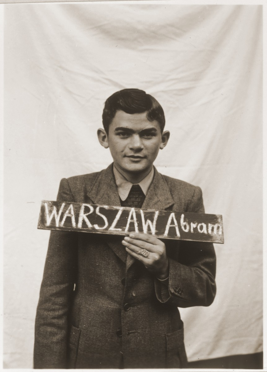 Abram Warszaw with a name card intended to help any of his surviving family members locate him at the Kloster Indersdorf DP camp.  This photograph was published in newspapers to facilitate reuniting the family.