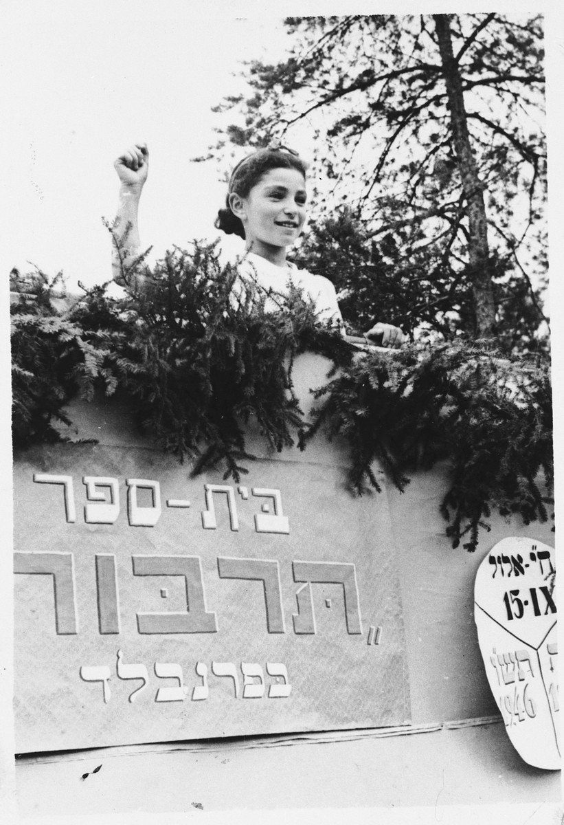 Chava Libestug poses above a sign for the Tarbut school in Foehrenwald.  She gave this photograph to her friend, Sonia Dzienciolski, shortly before she left the camp.