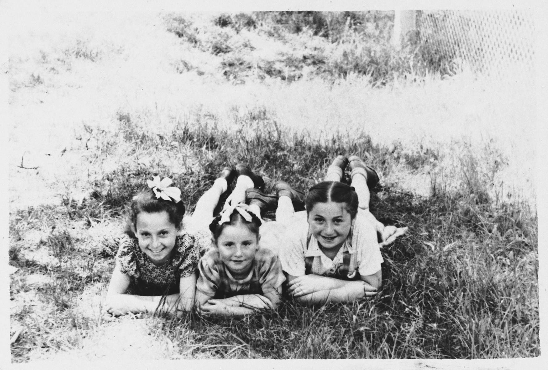 Sonia Dzienciolski and two friends lie down in a grassy field.