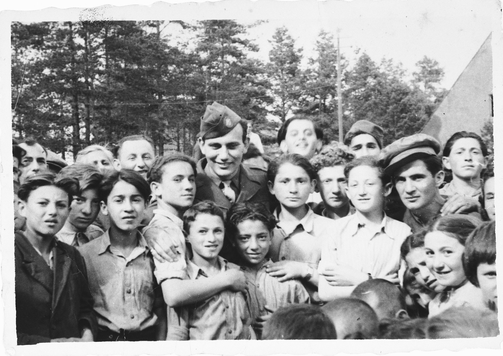 A large group of children gathers around an American soldier at the Foehrenwald displaced persons camp.  Among those pictured are Sonia Dzienciolski (bottom right) and  Paul Brottman among the children (lower left).