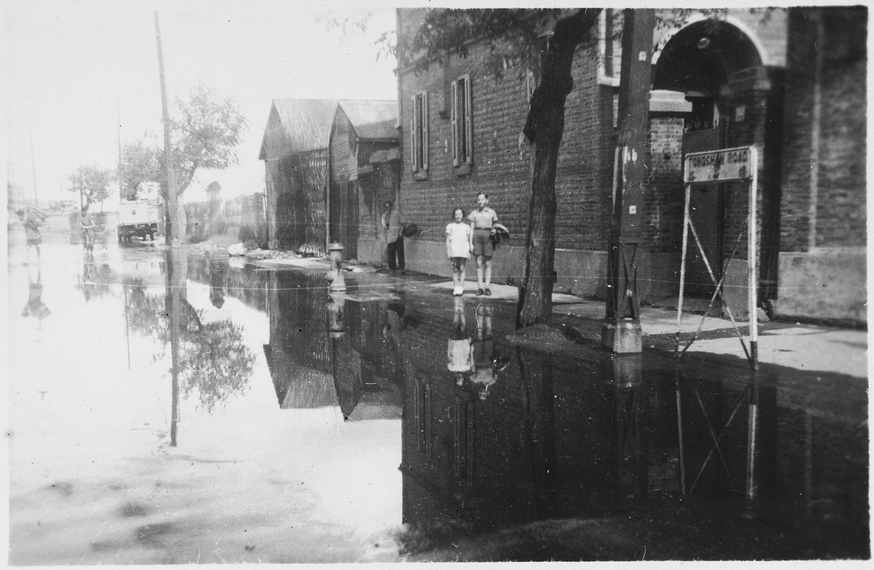 Peter and Marion Witting stand on a flooded street outside their home after a typhoon.