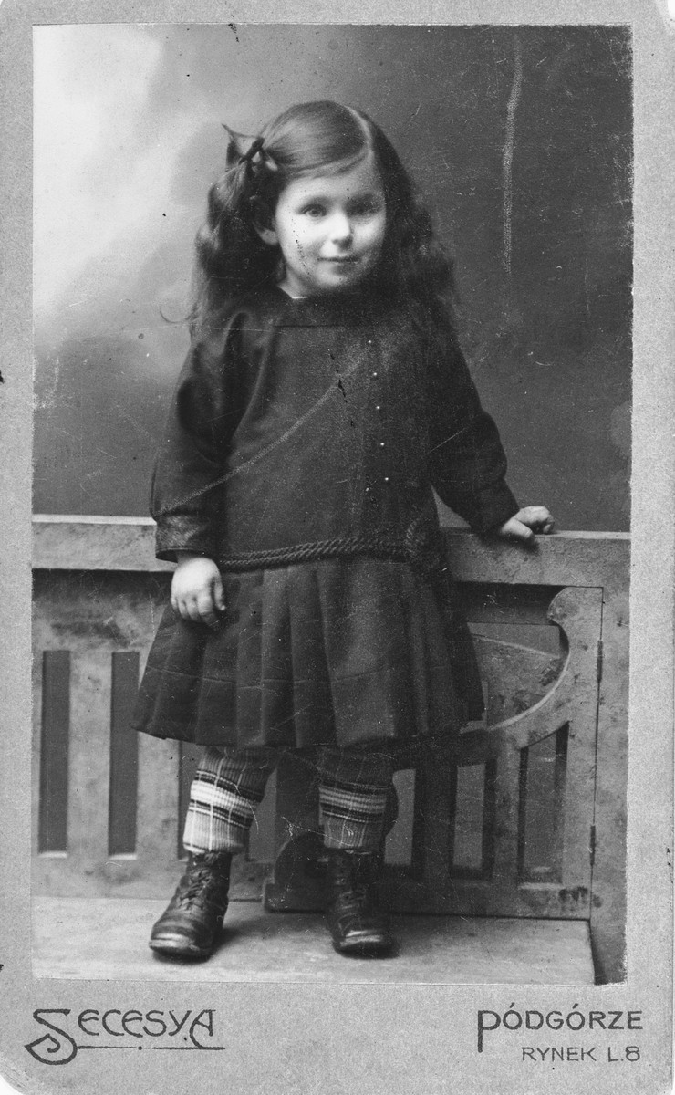 Studio portrait of Felicja Pleszowski as a young girl.  This photograph was part of an album that was saved and retrieved in the following manner.  After the war, Felicja was standing on a street corner in Krakow waiting for a bus.  A total stranger approached her and told her that she recognized her from her photographs.  The Polish woman had moved into the Klopholcz's apartment and found Felicja's photo album and autograph book from school.  The Polish woman had saved the two albums and after bumping into Felicja by pure chance, she returned the books to her.