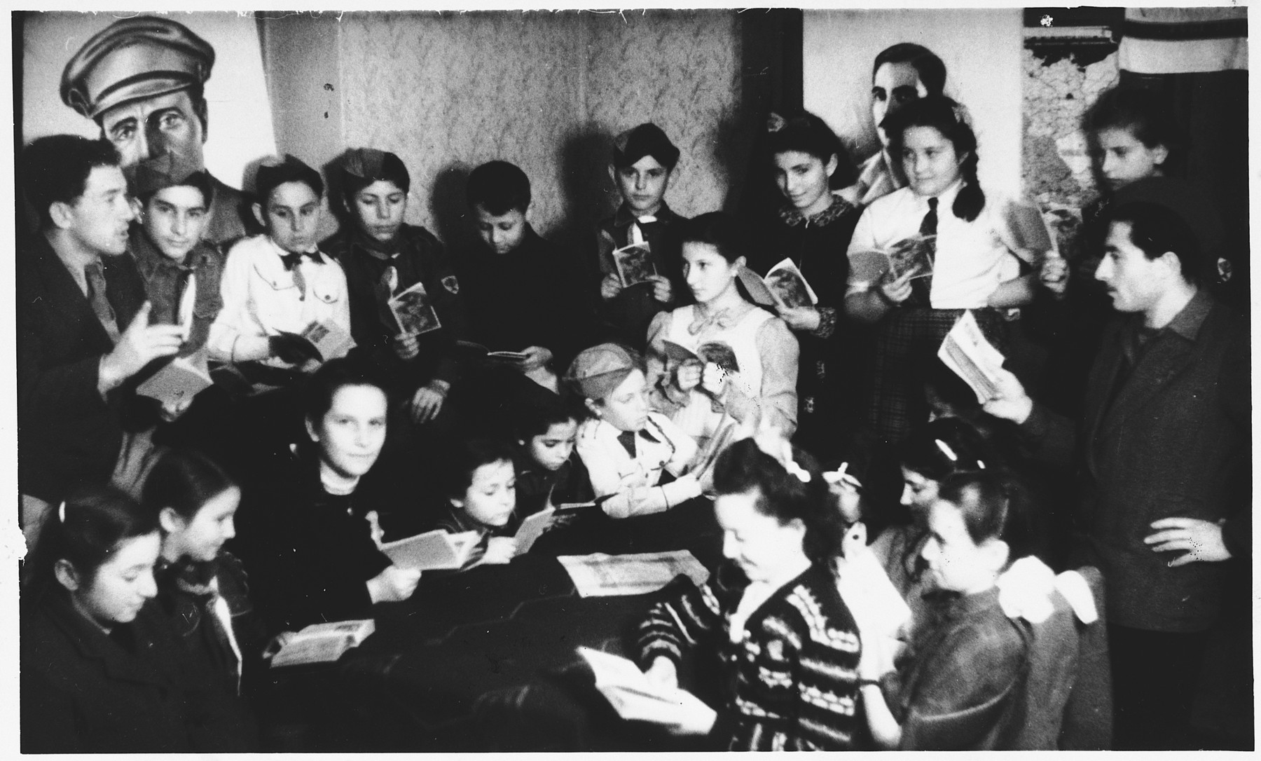 Children in the Foehrenwald displaced persons camp read together during a meeting beneath a portrait of Joseph Trumpeldor.