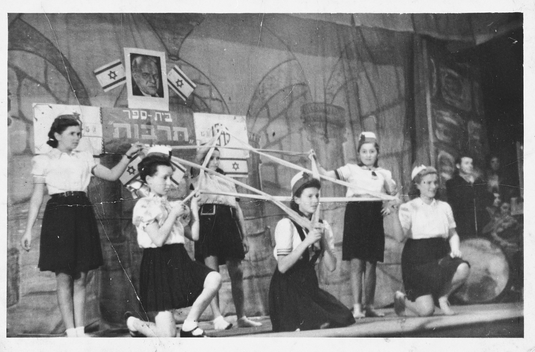Children make a Jewish star out of ribbon during a performance at the Foehrenwald displaced persons camp.