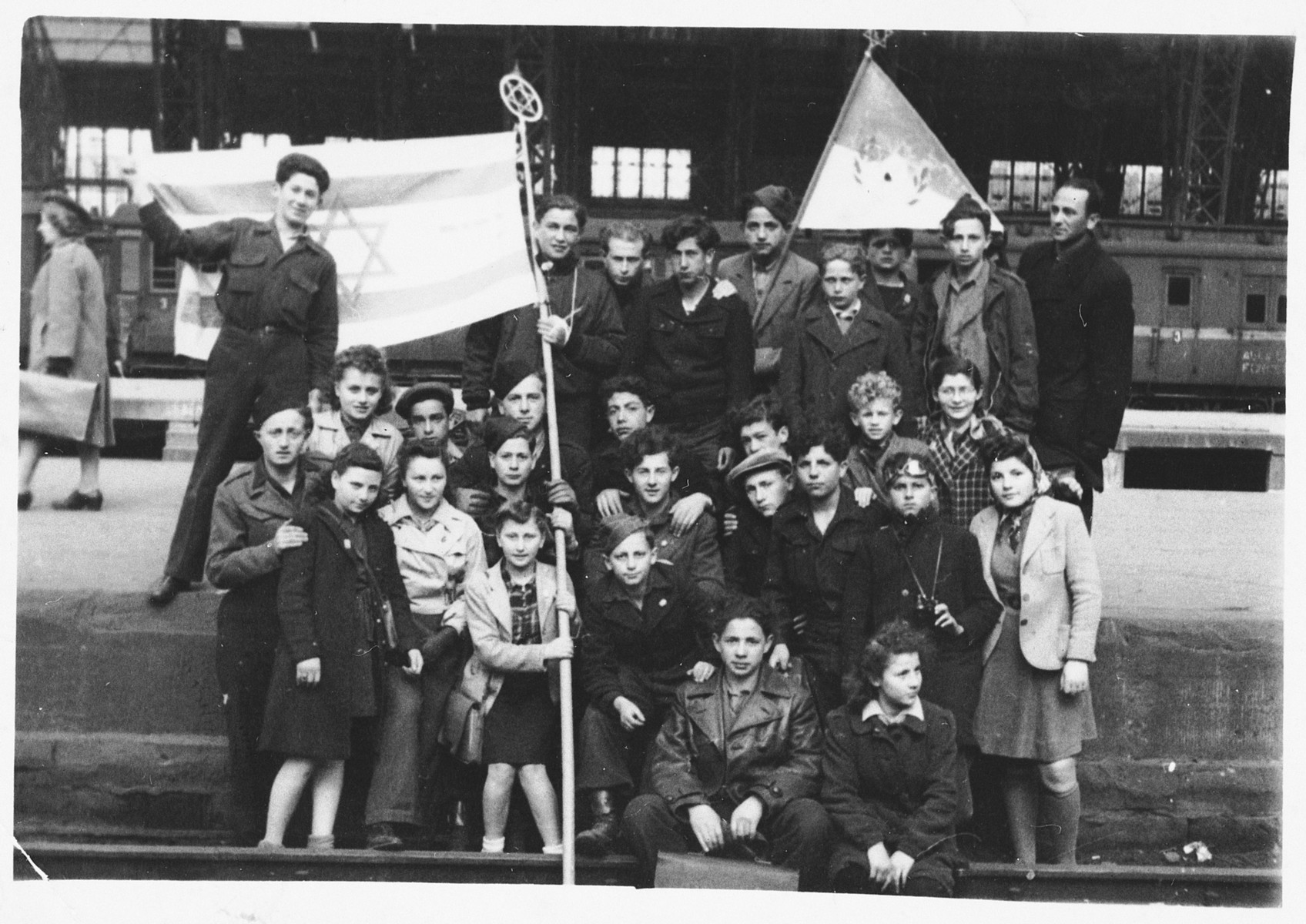 Teenagers from the Zeilsheim children's center pose together with a Zionist flag.  Among those pictured are Eliezer Rosenbach and Shlomo Wacs.