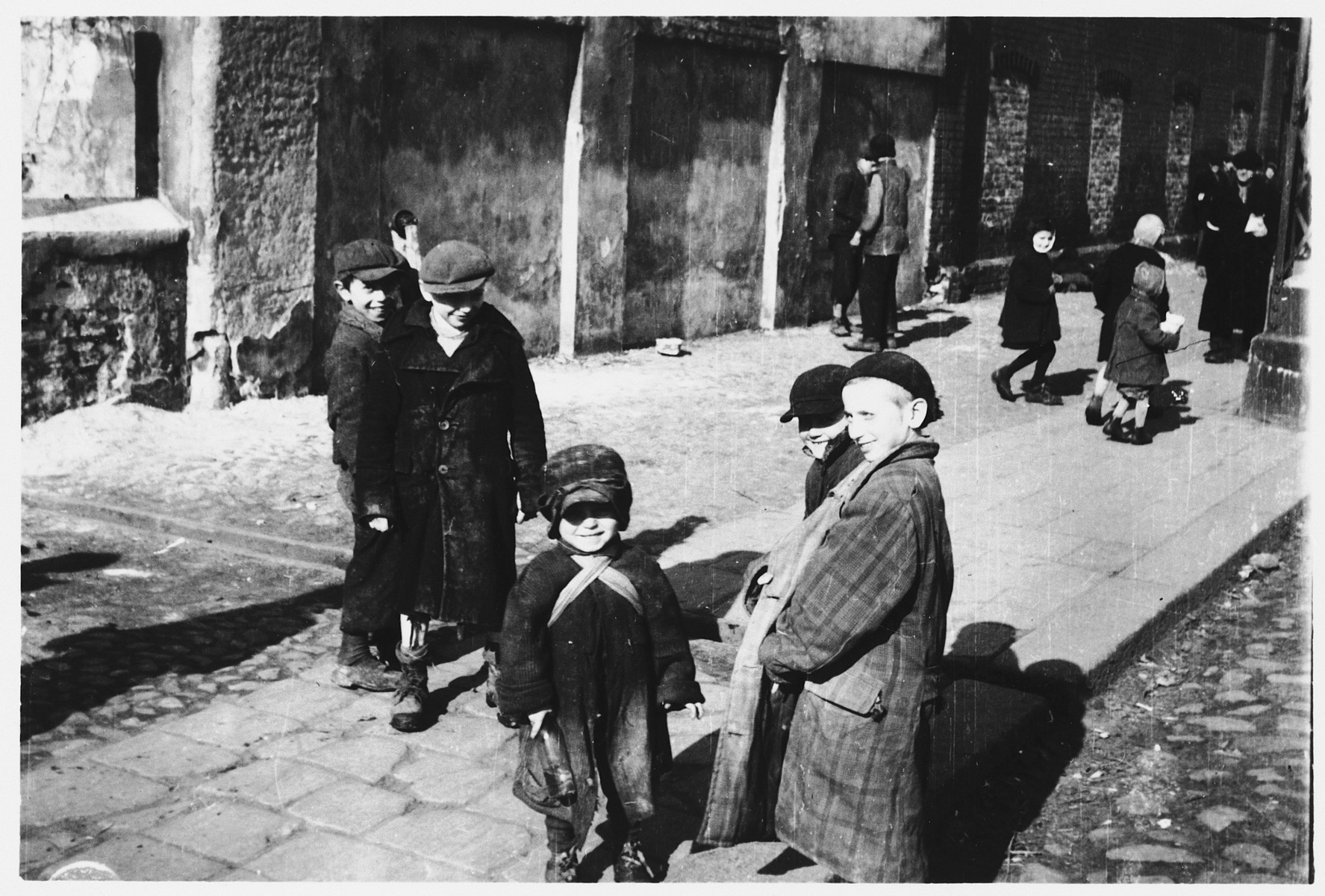 A group of children are gathered on a street corner in the Warsaw ghetto.