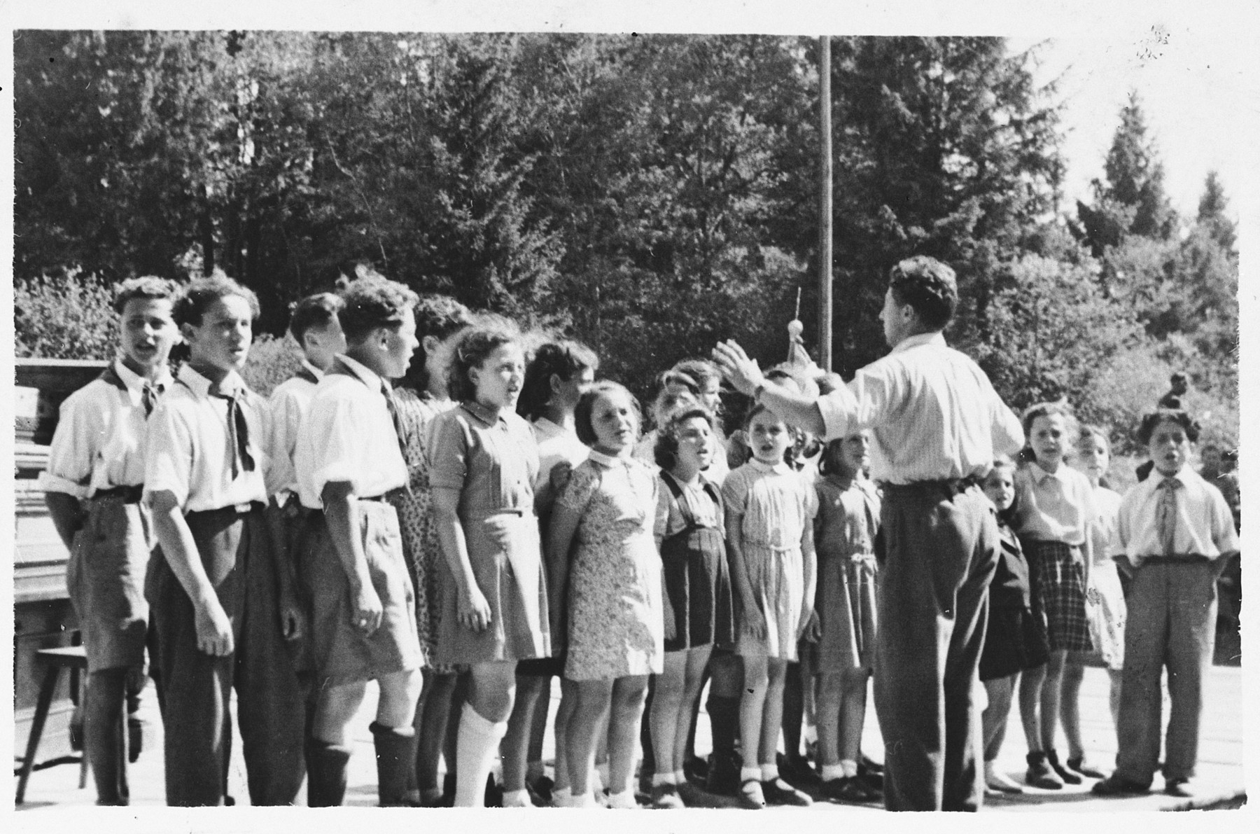Children sing in a Lag BaOmer celebration at the Foehrenwald displaced persons camp.  Leading the singing is Stanley (Shlomo) Zektzer.