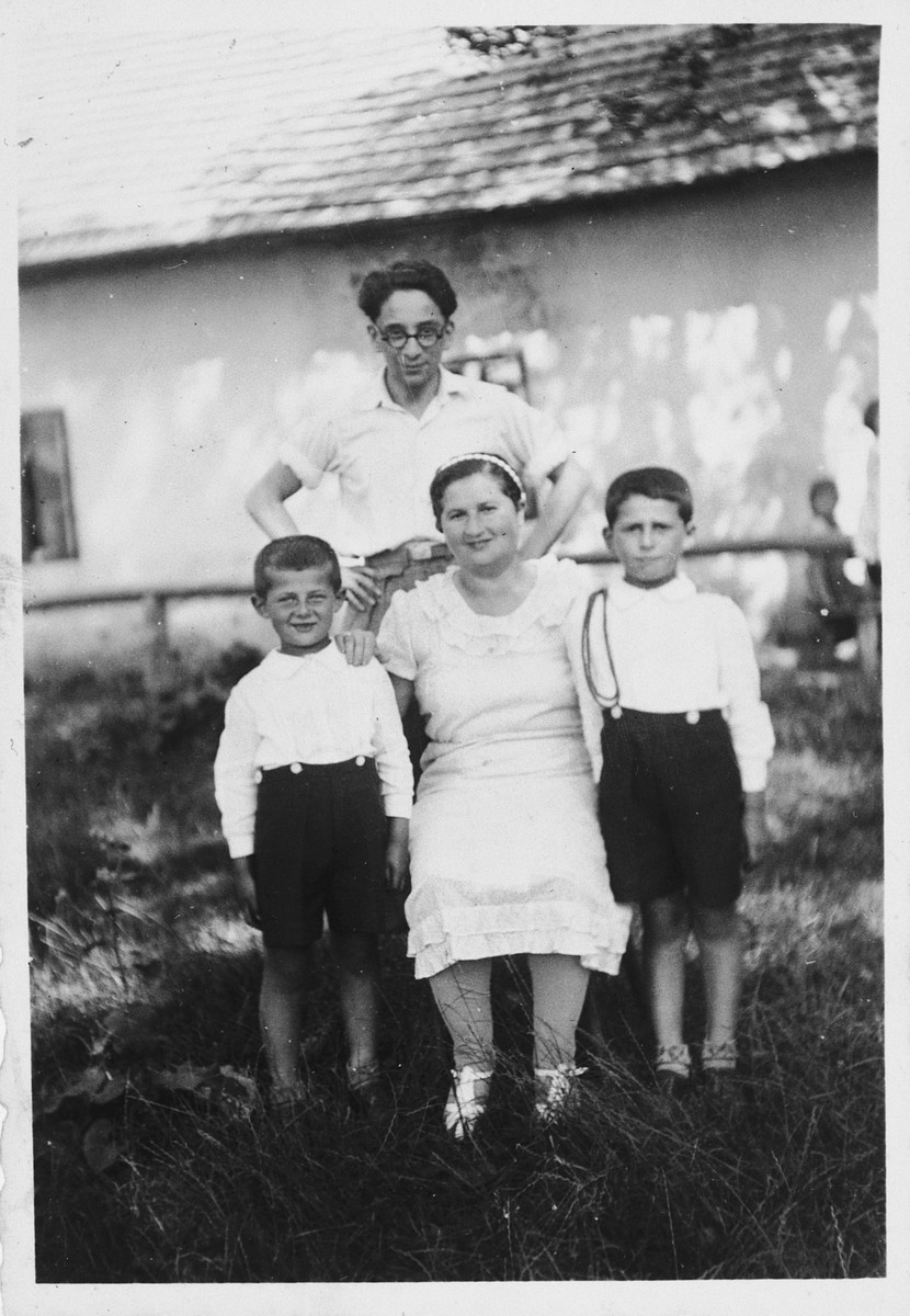 Ewa Rosenbach poses with her two sons and a neighbor in front of her home in rural Poland.