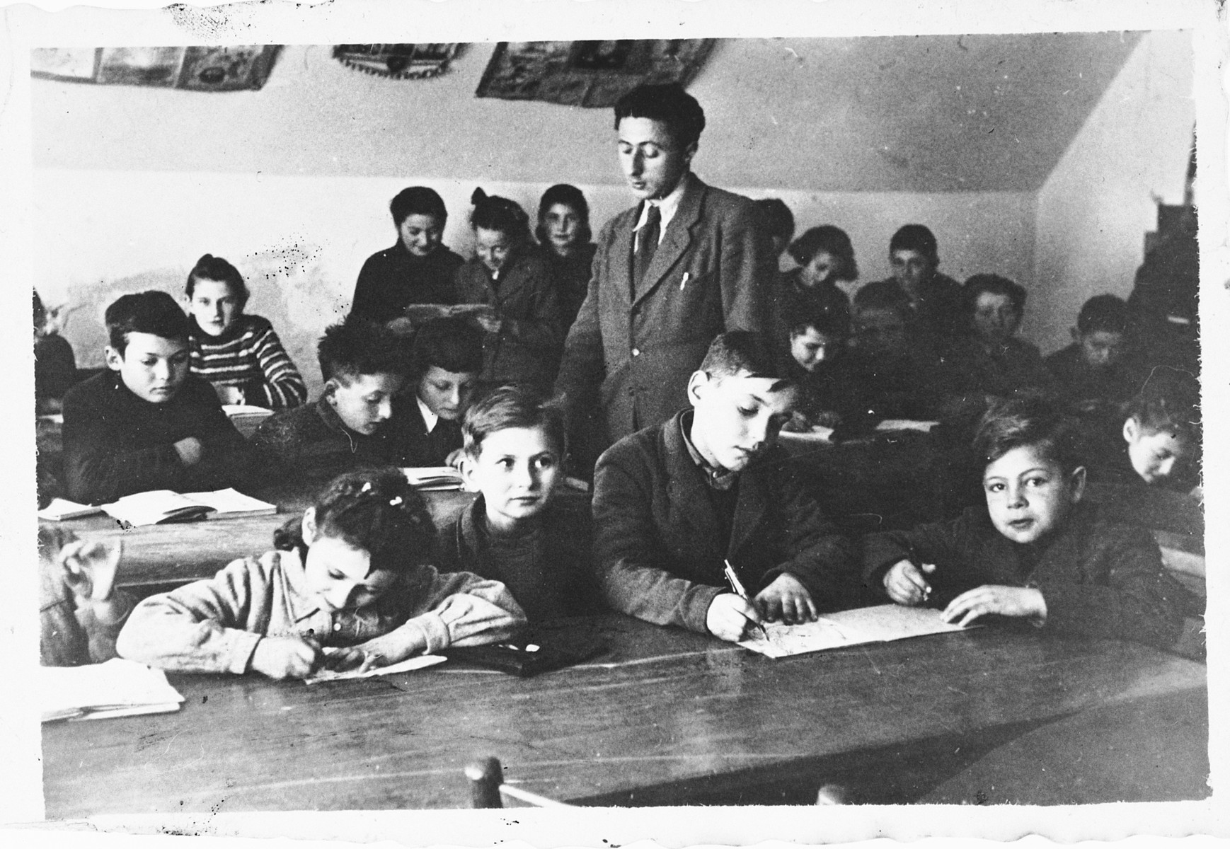 Children study at their desks in a school in the Foehrenwald displaced persons camp.  Among those pictured is the teacher, Stanley (Shlomo) Zektzer.
