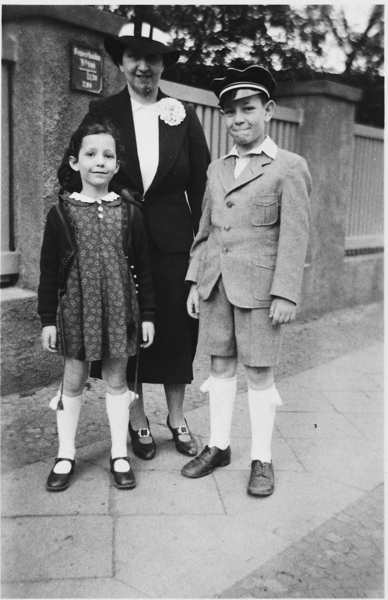 Peter Witting, wearing his school cap, poses on a sidewalk with his mother and sister.