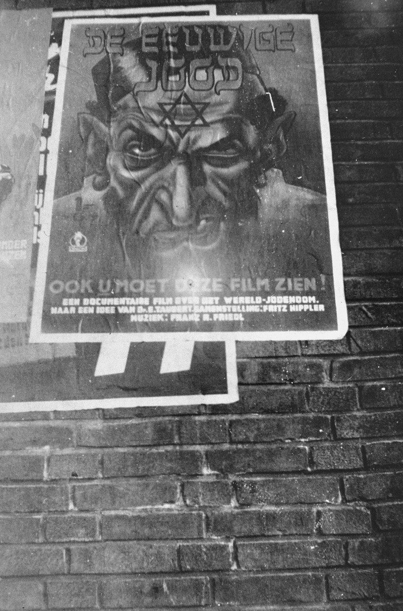 "A poster advertising the anti-Semitic propaganda film ""Der ewige Jude"" (the Eternal Jew) hangs on the side of a Dutch building.    This photograph was taken clandestinely by the donor, Samuel Schrjver."