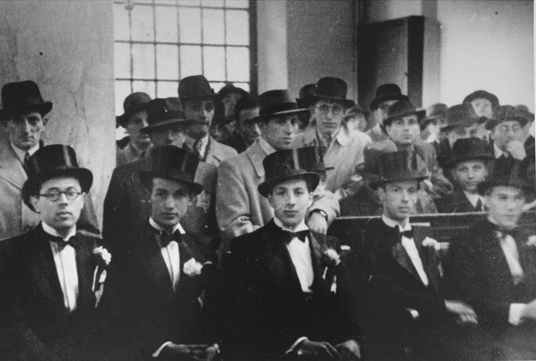 Male attendants at the wedding of Herman de Leeuw and Annie Pais sit in a pew of the Sephardic synagogue in the Jewish quarter of Amsterdam.    Pictured in the front row, third from the left, is Samuel Schrijver.