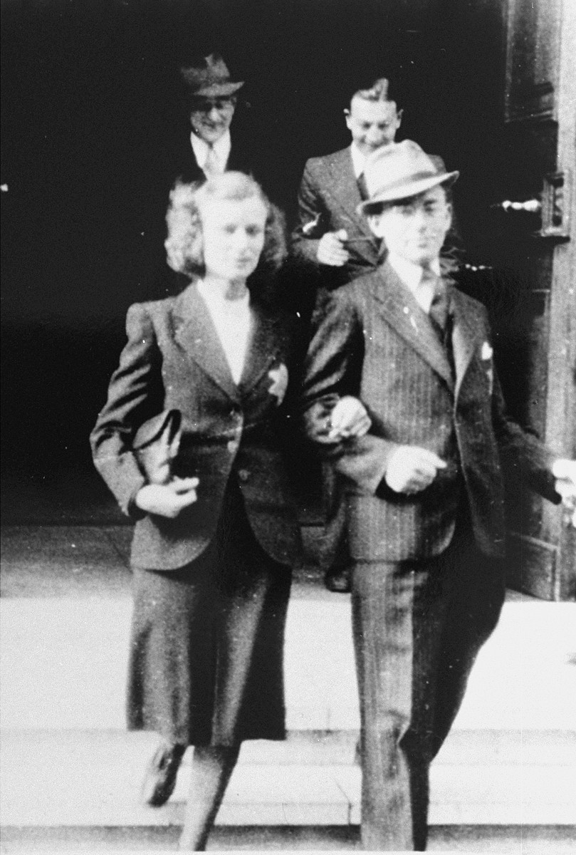 A newlywed Jewish couple, Mauritz Wijnberg and Betje Jakobs, emerge from a building on their wedding day wearing Jewish badges.