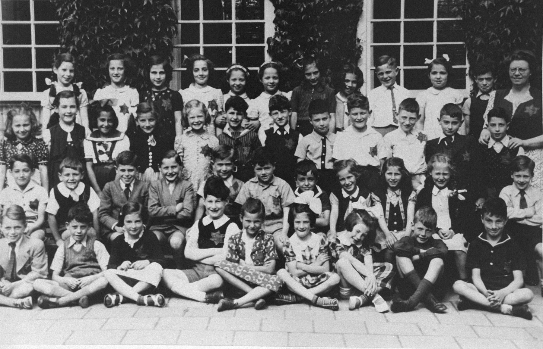 Students of the Jewish school on the Jan van Eyckstraat in Amsterdam.  Most of the children are wearing the Jewish badge.  Pictured second from the right in the second row is Yoka Verdoner, who survived the war in hiding.