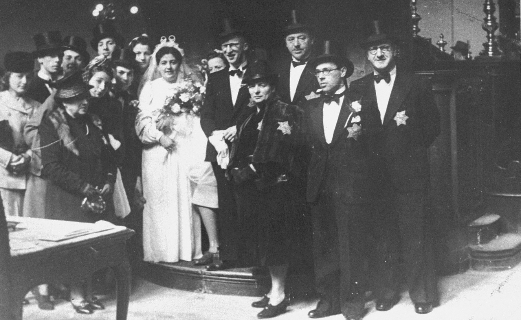 The newly married couple, Herman de Leeuw and Annie Pais, pose with members of the wedding party shortly after the ceremony.    Pictured from left to right are Fifi Sjouwerman, Sieg Pekel, Mrs. Pais (the bride's mother), Jaap de Leeuw (Fifi's fiancé), Rachel de Leeuw (the groom's sister), Samuel Schrijver, S. Barzilay (Rachel's fiancé), Ida de Leeuw, Anne de Leeuw-Pais, Ina de Leeuw, Herman de Leeuw, Heintje de Leeuw (the groom's mother), Jacques Pais (the bride's father), Abraham Pais (the bride's brother), and Sam de Leeuw (the groom's father).