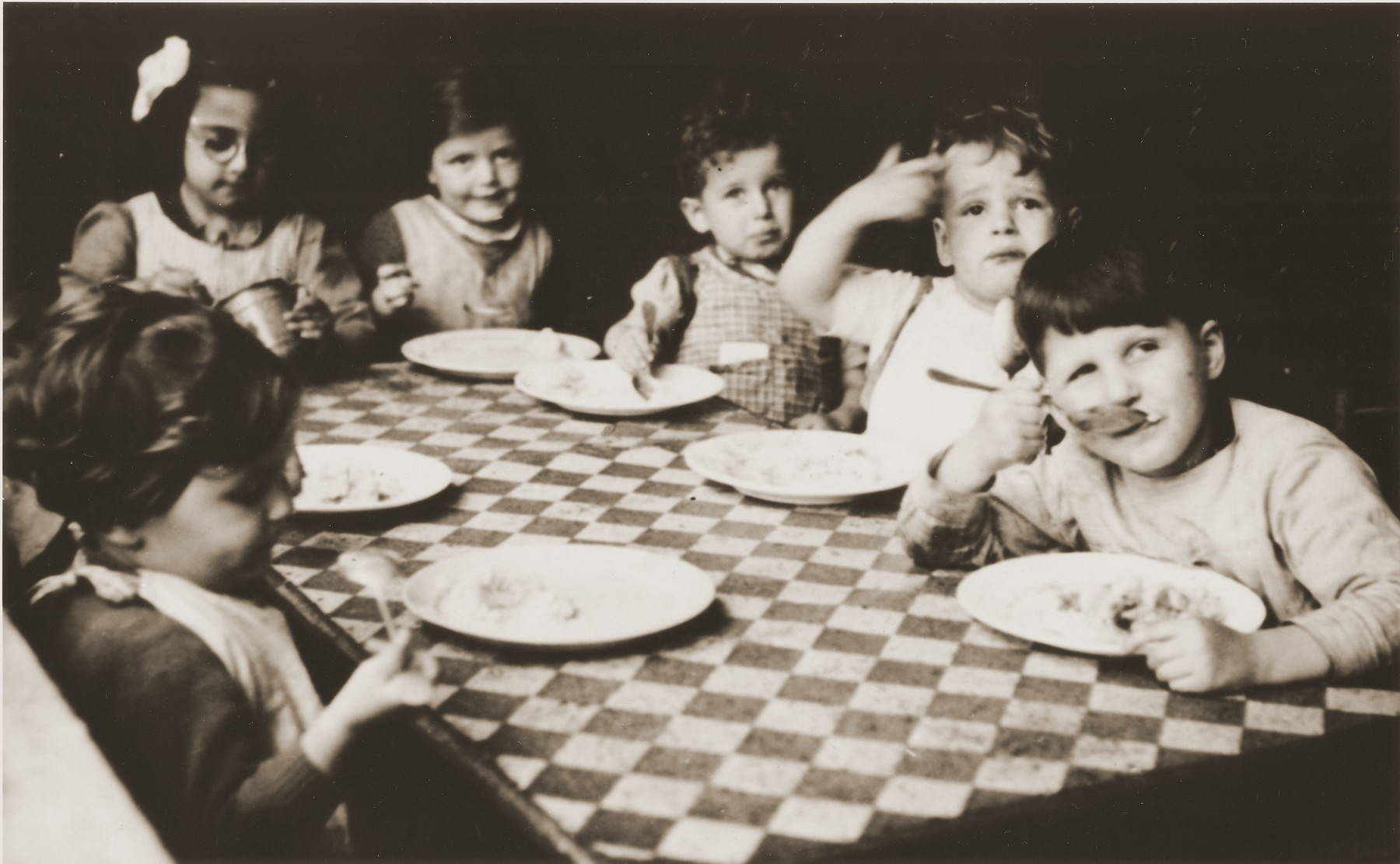 Toddlers at the La Pouponniere children's home in Belgium are seated around a table eating.