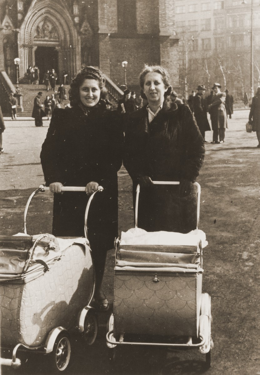 Two Czech Jewish women push baby carriages through a public square in Prague.  Pictured from left to right are Erika (Neuman) Kauder and her mother, Dolly Neuman.