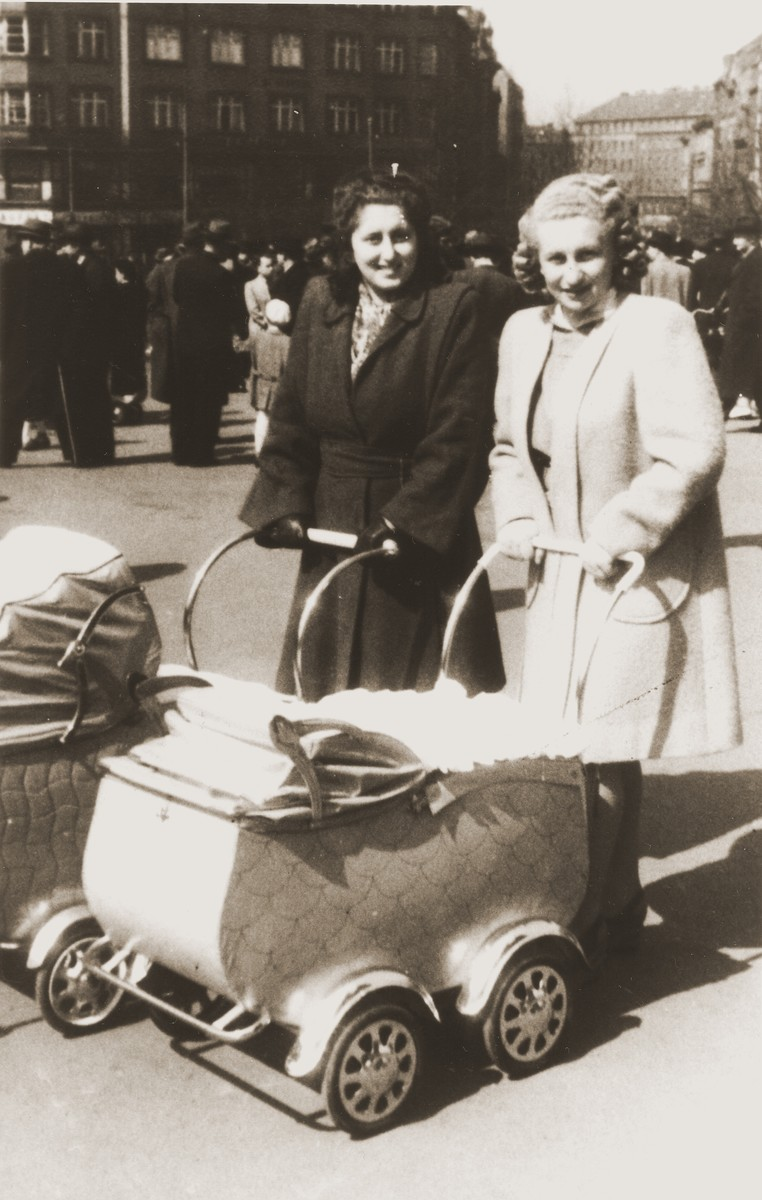 Two Czech Jewish women push baby carriages along a street in Prague.  Pictured from left to right are Erika (Neuman) Kauder and her sister, Beatrice (Neuman) Rada.