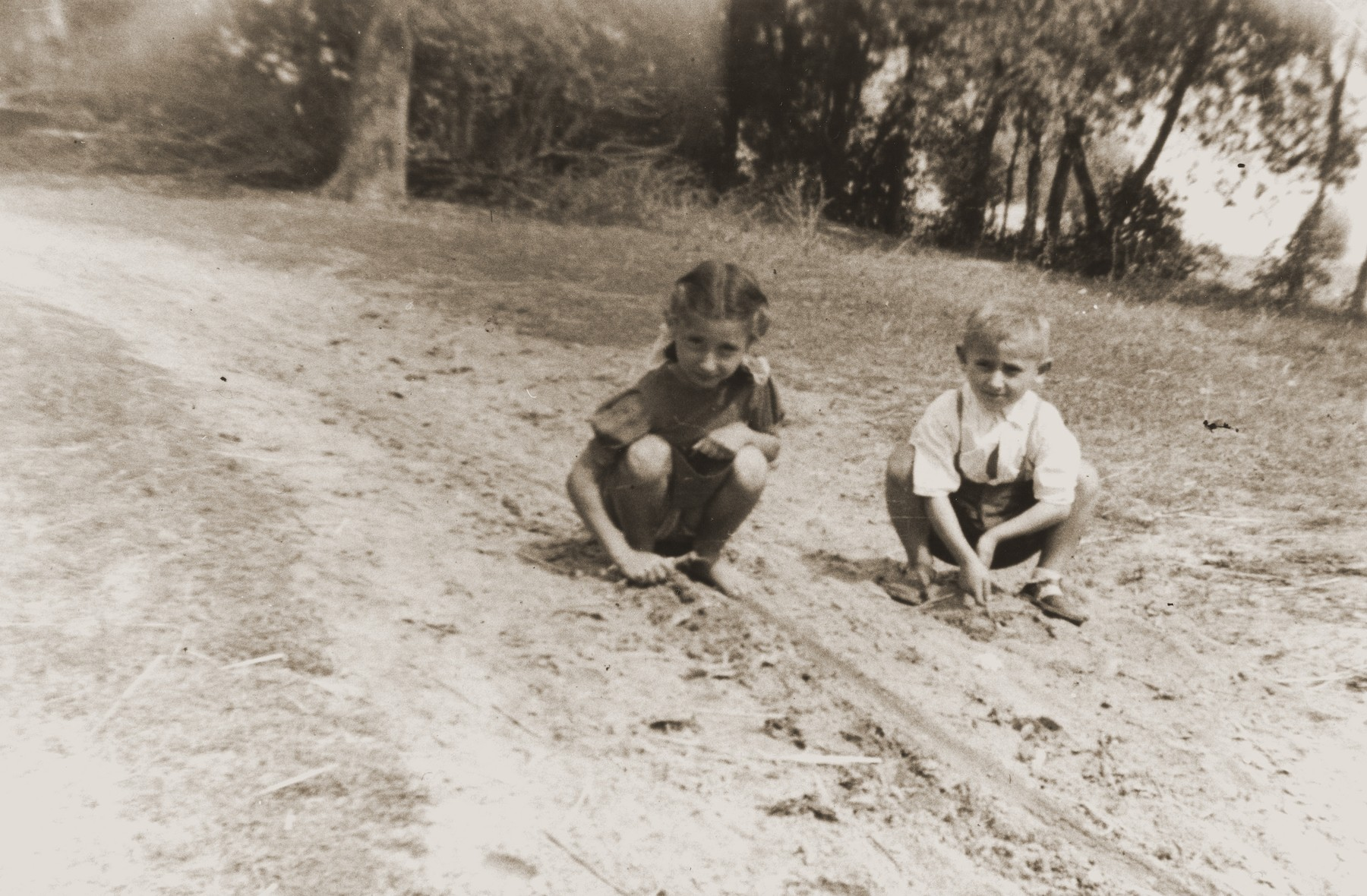 Zofja Fajnsztejn, a Jewish child in hiding, plays with a Polish child in a Warsaw park.