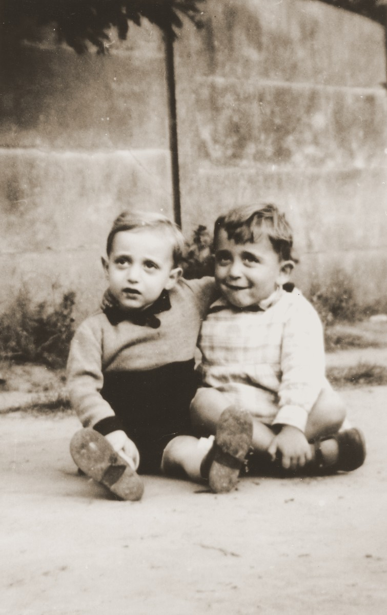 Two young children sit outside the La Pouponniere children's home in Uccle.