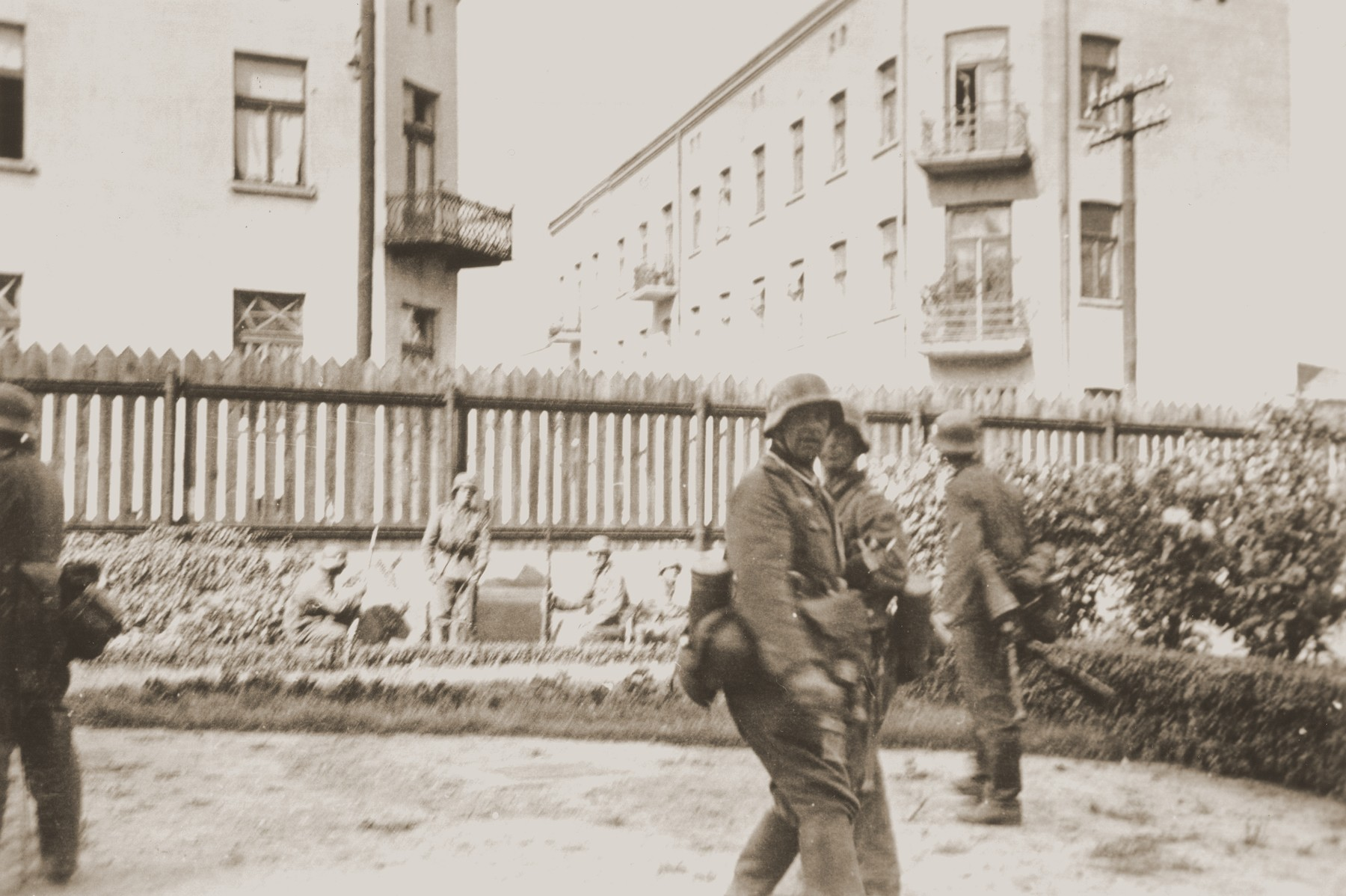 "German soldiers patrol a street in Czestochowa.    The German inscription on the back of the photograph reads, ""They [Polish snipers] shot at us from this house"" [the apartment building on the right behind them].  One photograph from an album belonging to a member of a Wehrmacht machine gunners' unit, which was found after the war by Lorenzo Hawkins (the donor's grandfather), an American serviceman in Company B, 56th Armored Engineer Battalion."