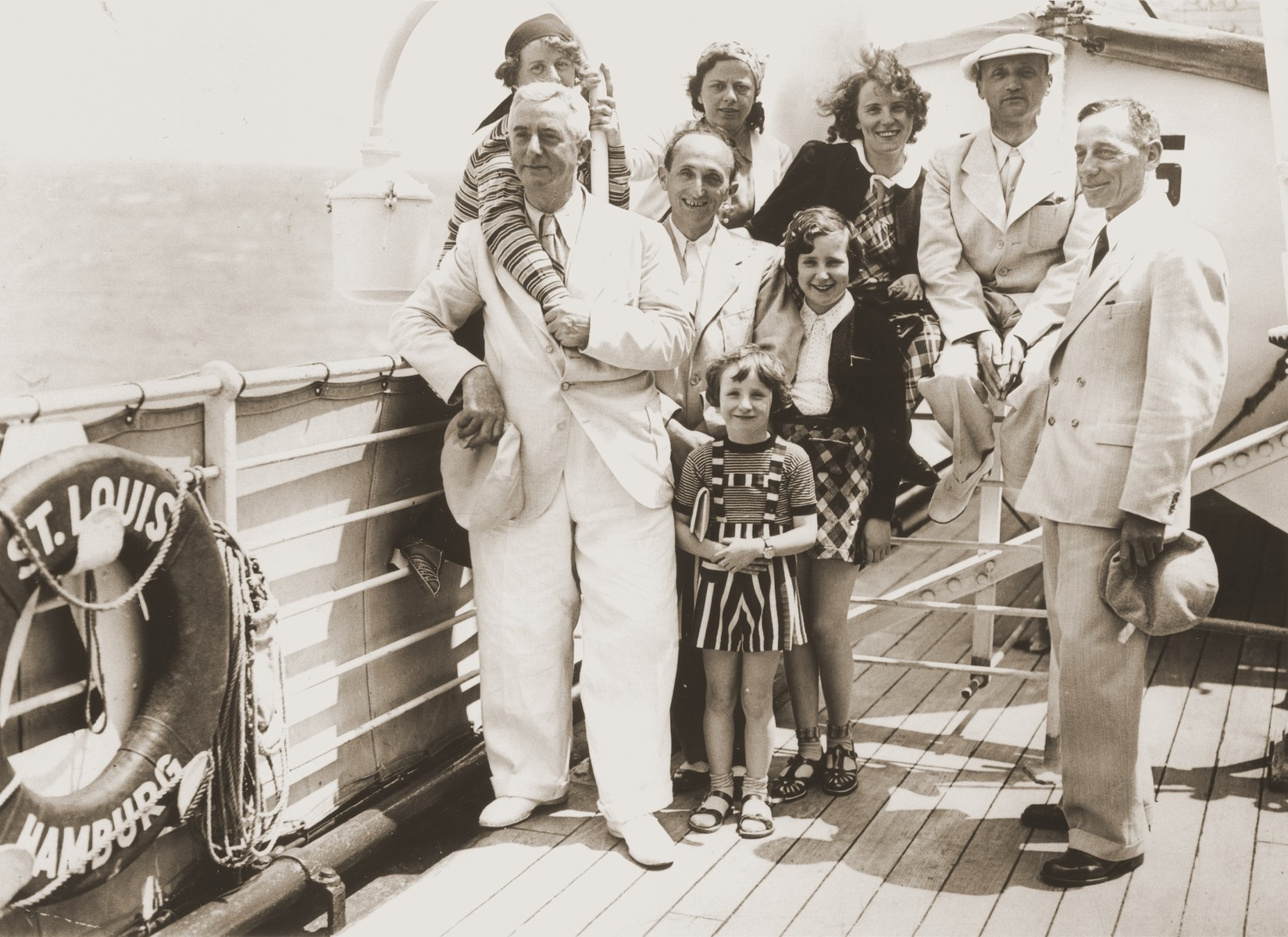 Members of the Dublon family pose on the deck of the MS St. Louis.  Willi Dublon stands second from the left.  Erna and Erich are sitting on the railing to his right.  Eva and Lore stand in front.